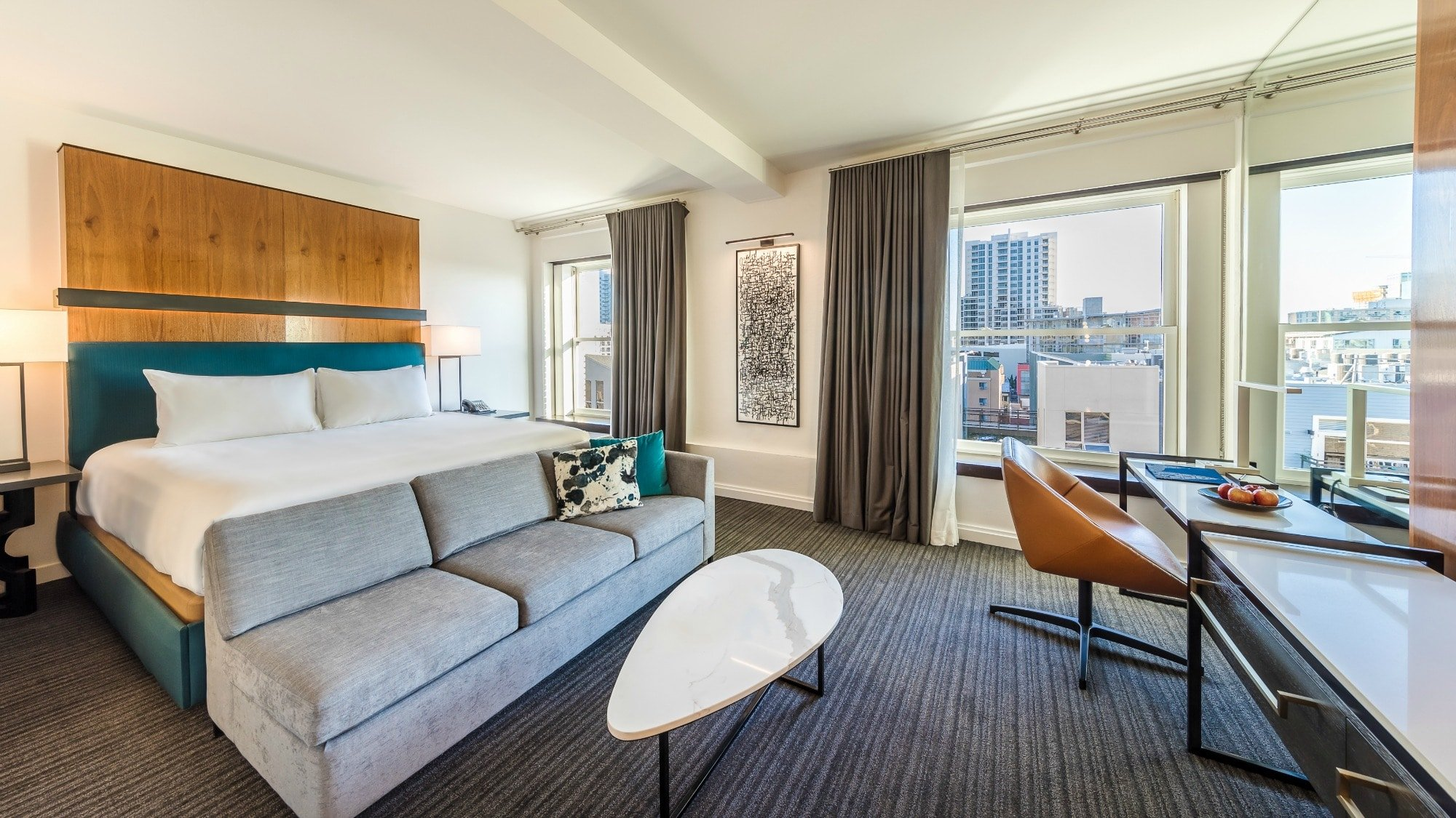 A king room with coastal grey colors, view of downtown and a pop of turquoise around the bed at Andaz San Diego.