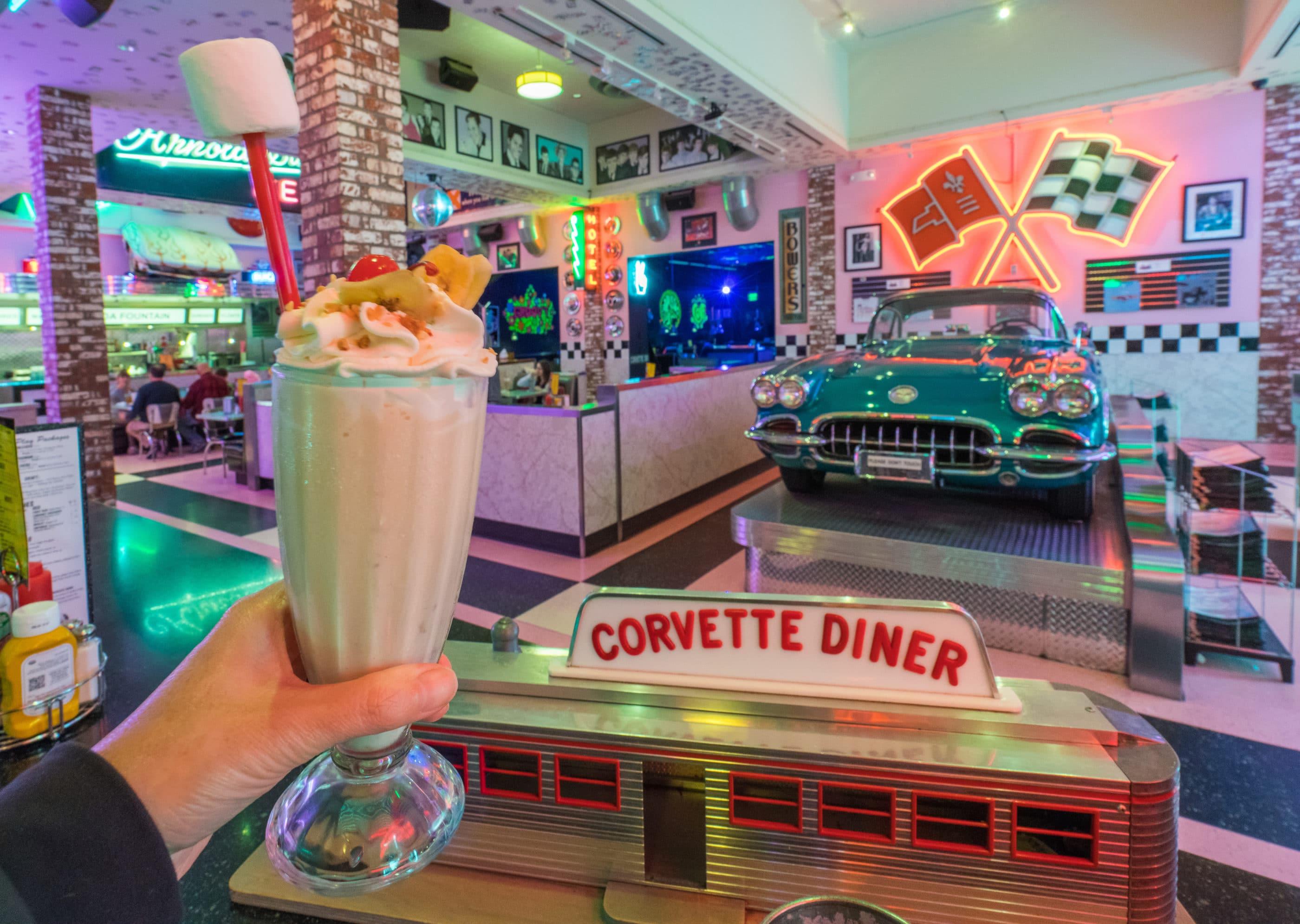 A giant milkshake held up in front of vintage Corvette inside the kid-friendly San Diego restaurant, Corvette Diner.