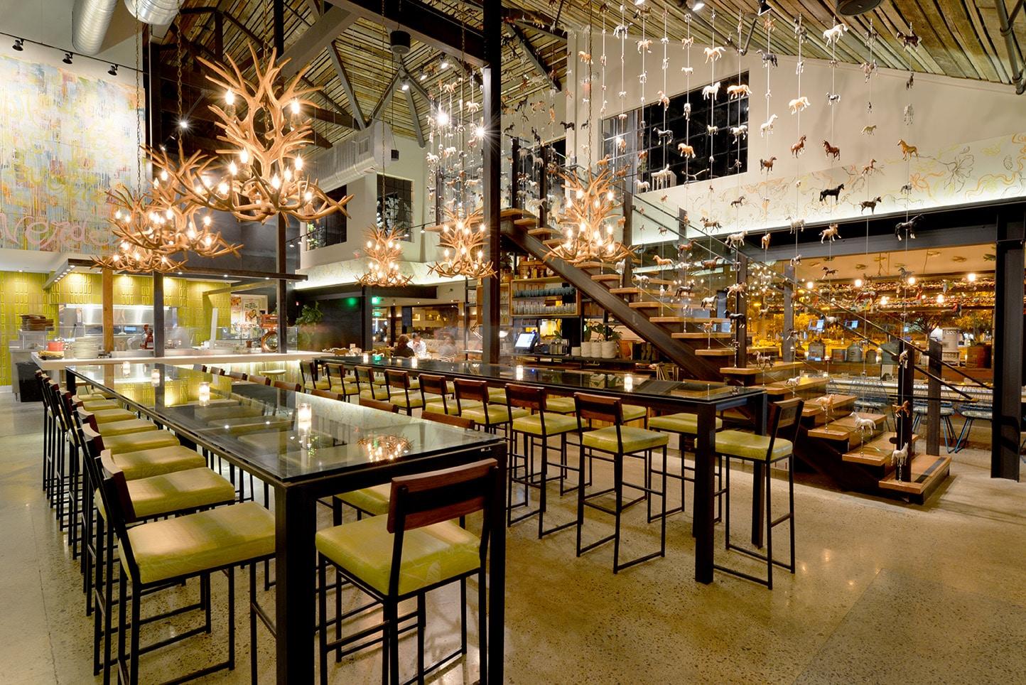 The contemporary interior of Cucina enoteca with deer antler light fixtures an industrial decor.