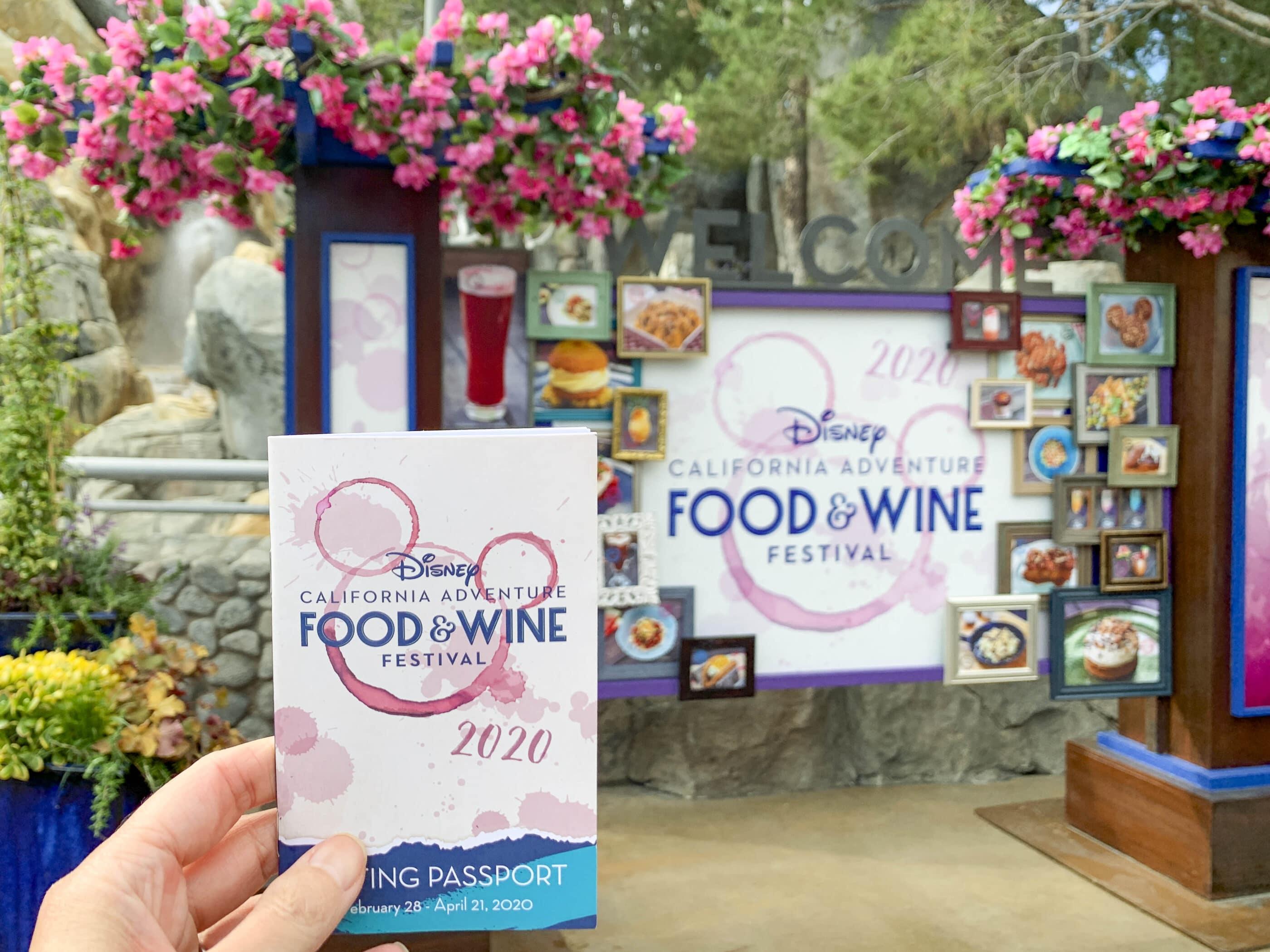 Je détiens le passeport de dégustation du Disney California Adventure Food and Wine Festival devant le grand panneau du festival.