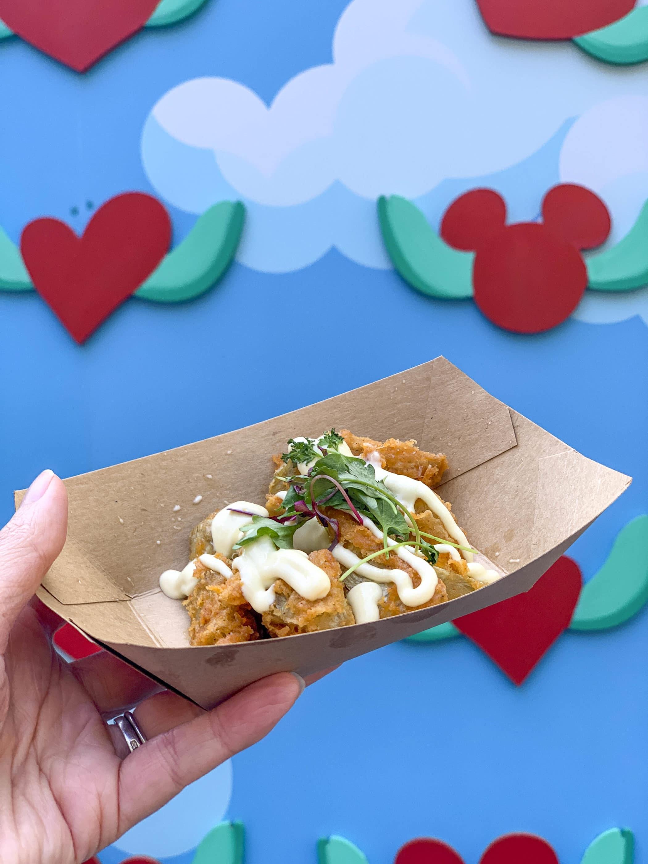 Un bac à papier avec les coeurs d'artichauts frits avec de l'aïoli au citron devant la murale du marché avec des coeurs et un Mickey caché.