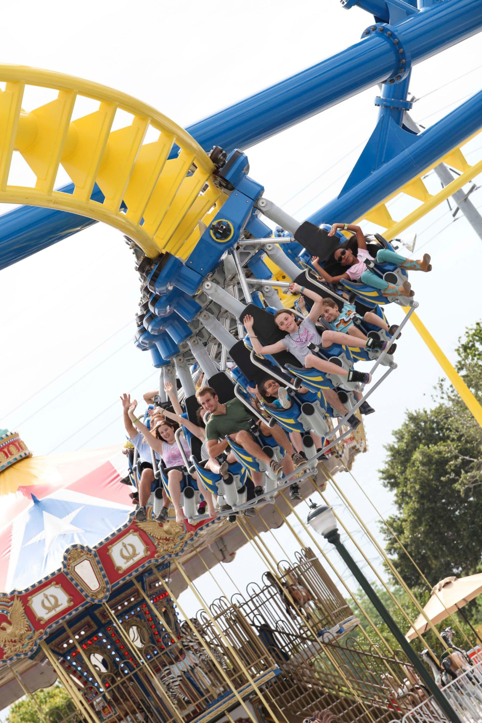 Families hang in seats on a roller coaster track at Fun Spot America i Orlando.