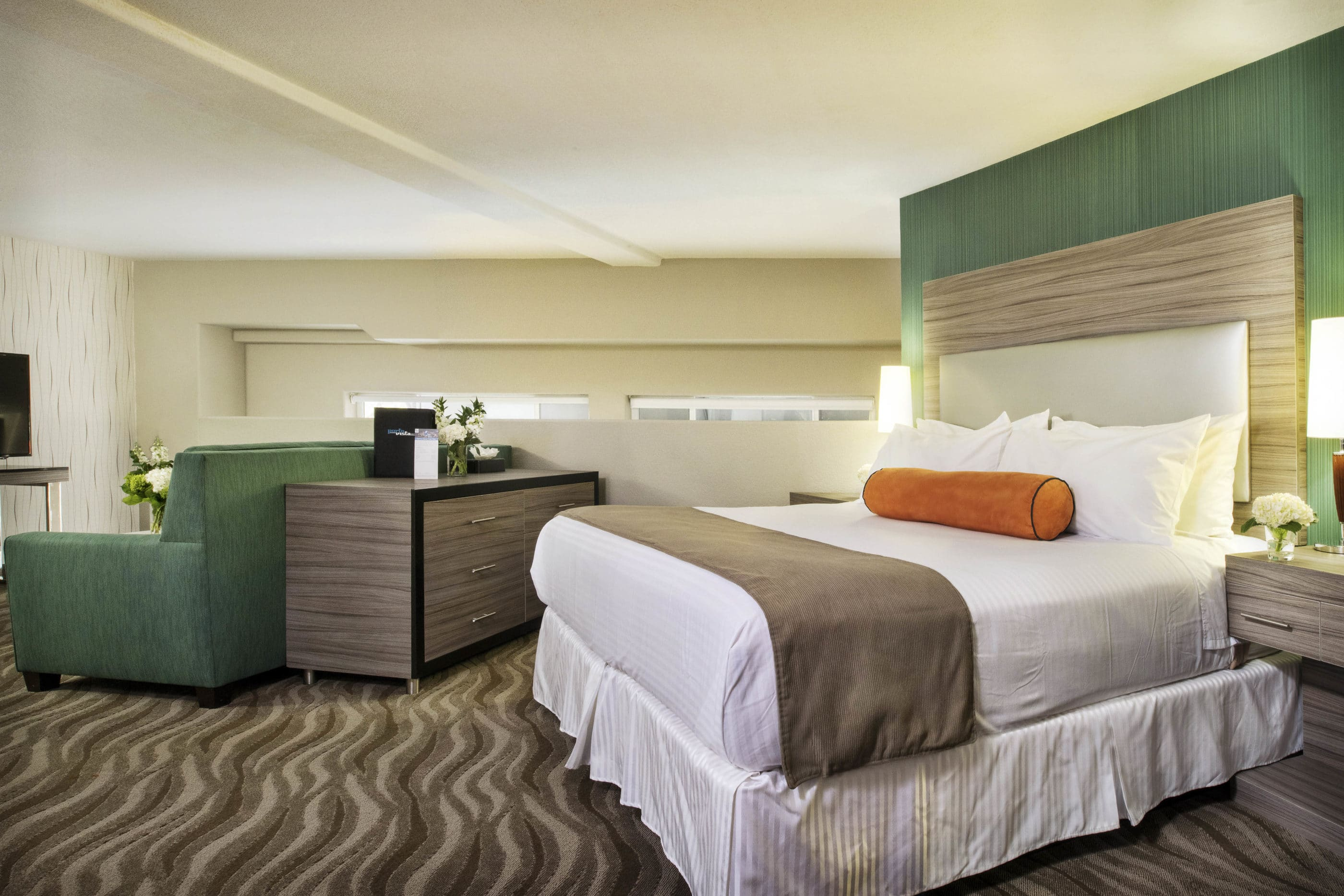 A room interior with neutral colors accented by green and orange at Porto Vista Hotel near San Diego Zoo.