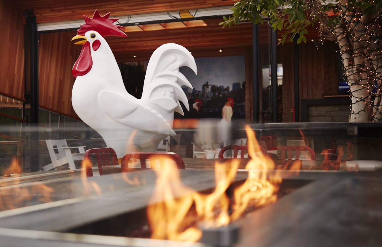 The giant chicken stands tall amid the outdoor seating at Crack Shack, a family-friendly restaurant in Little Italy San Diego.