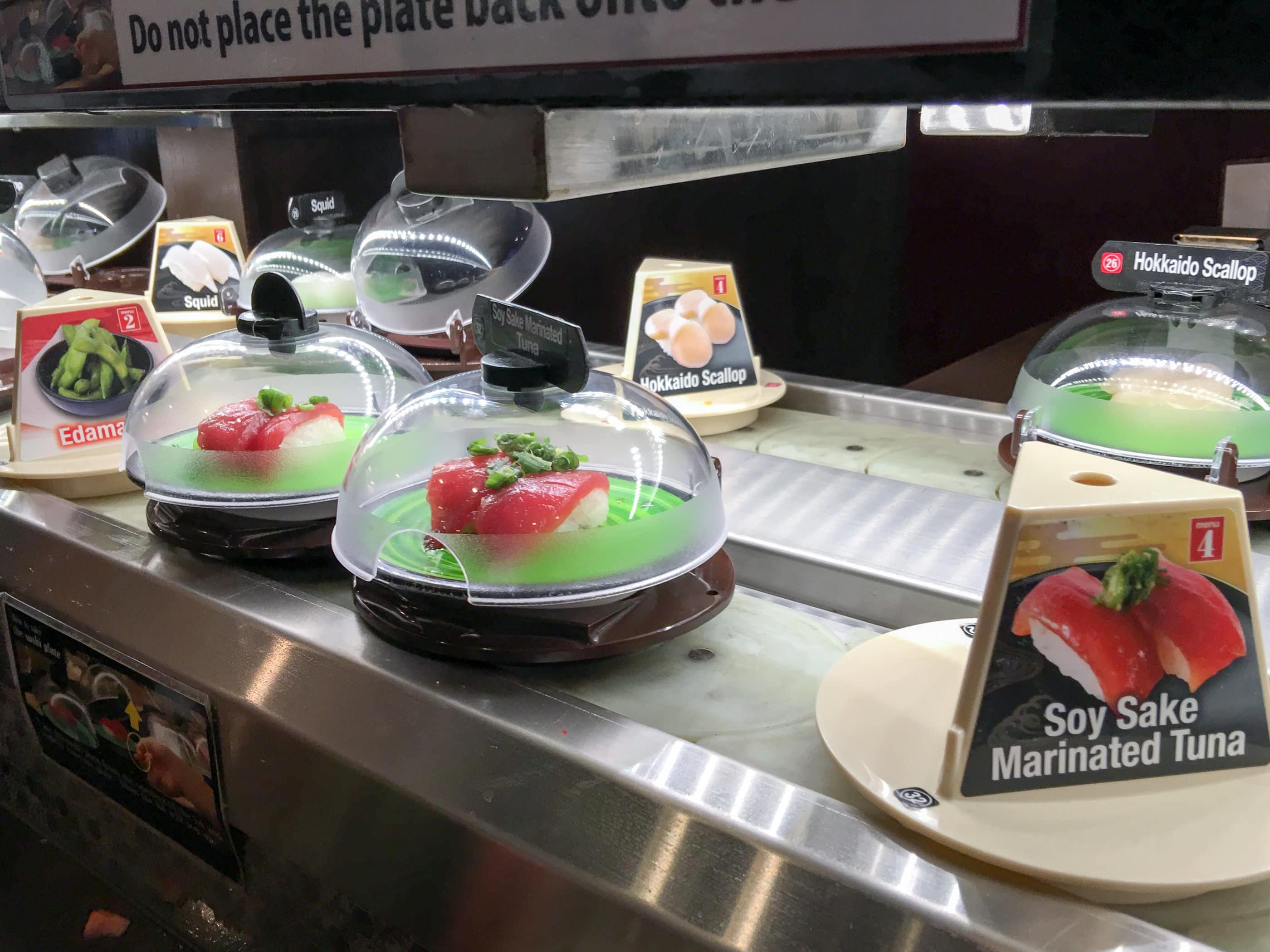 Tuna nigiri sushi under domes travels across a conveyor belt at Kura Sushi in San Diego.