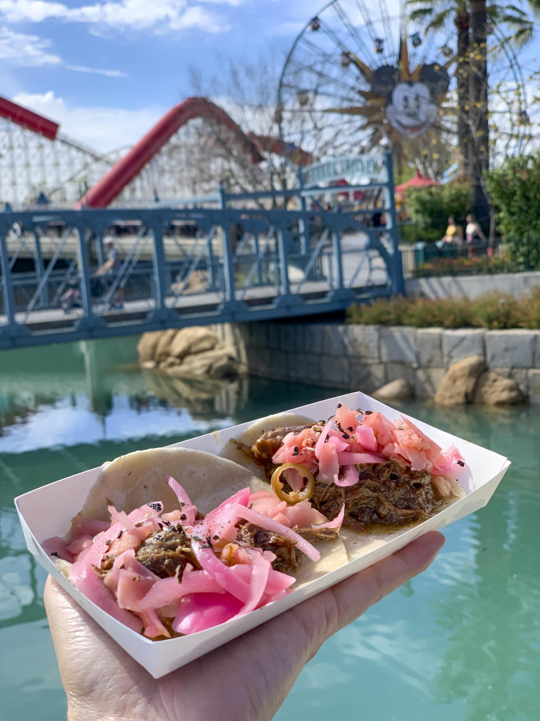 Tacos Barbacoa levés au-dessus de l'eau avec la grande roue Pixar Pal-A-Round en arrière-plan.