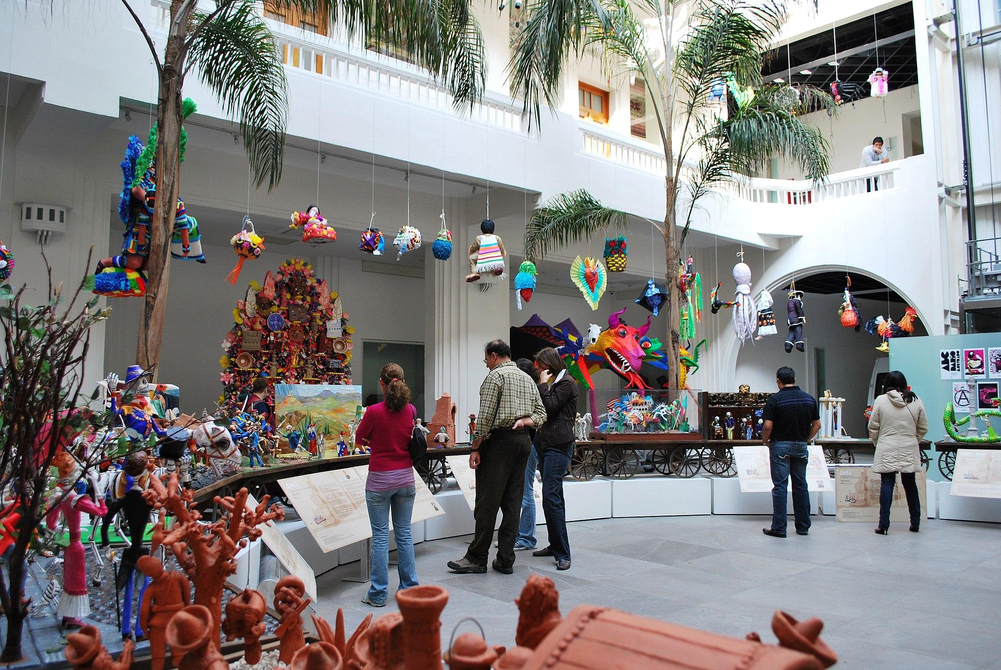 Guests at Museo de Arte Popular admire a Dia de los Muertos train display.