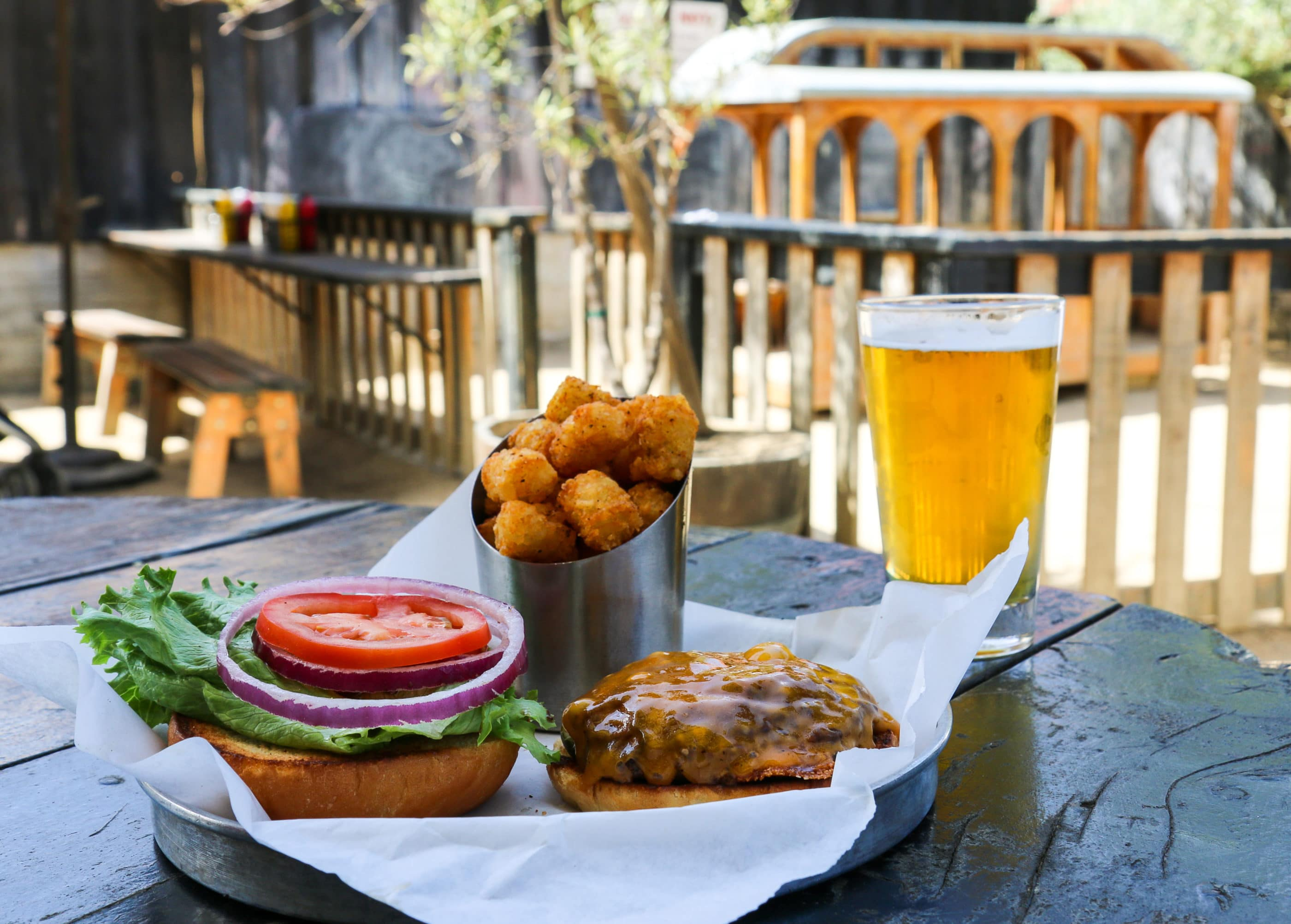 A burger, tater tots, and pint of local beer on a picnic table with the gated play area in the background at Station Tavern, a kid-friendly restaurant in San Diego.