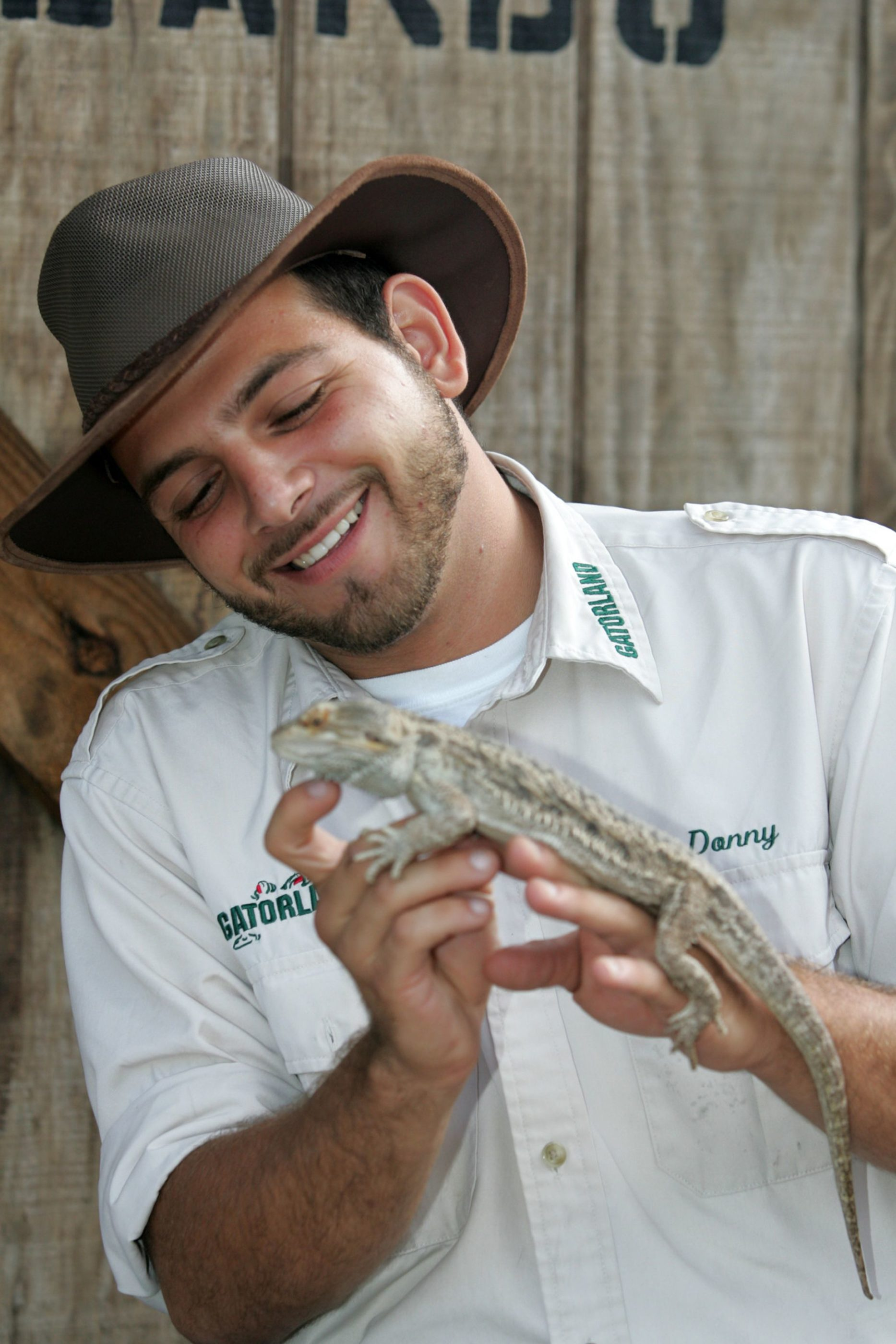 A staff member holds a small alligator at Gatorland in Orlando.
