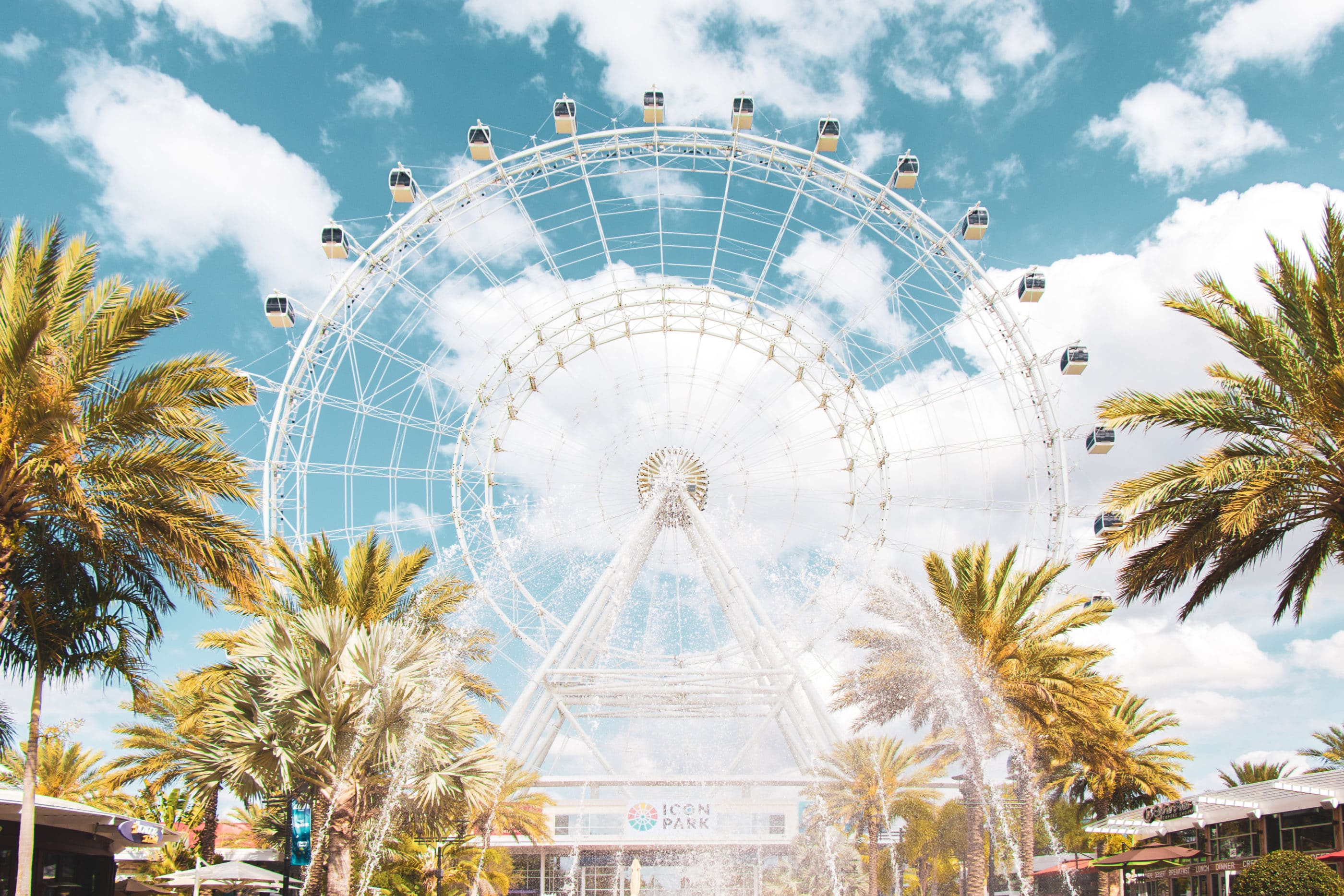 The Wheel at ICON Orlando spins against a blue sky with patches of clouds, one of the best things to do in Orlando with kids.