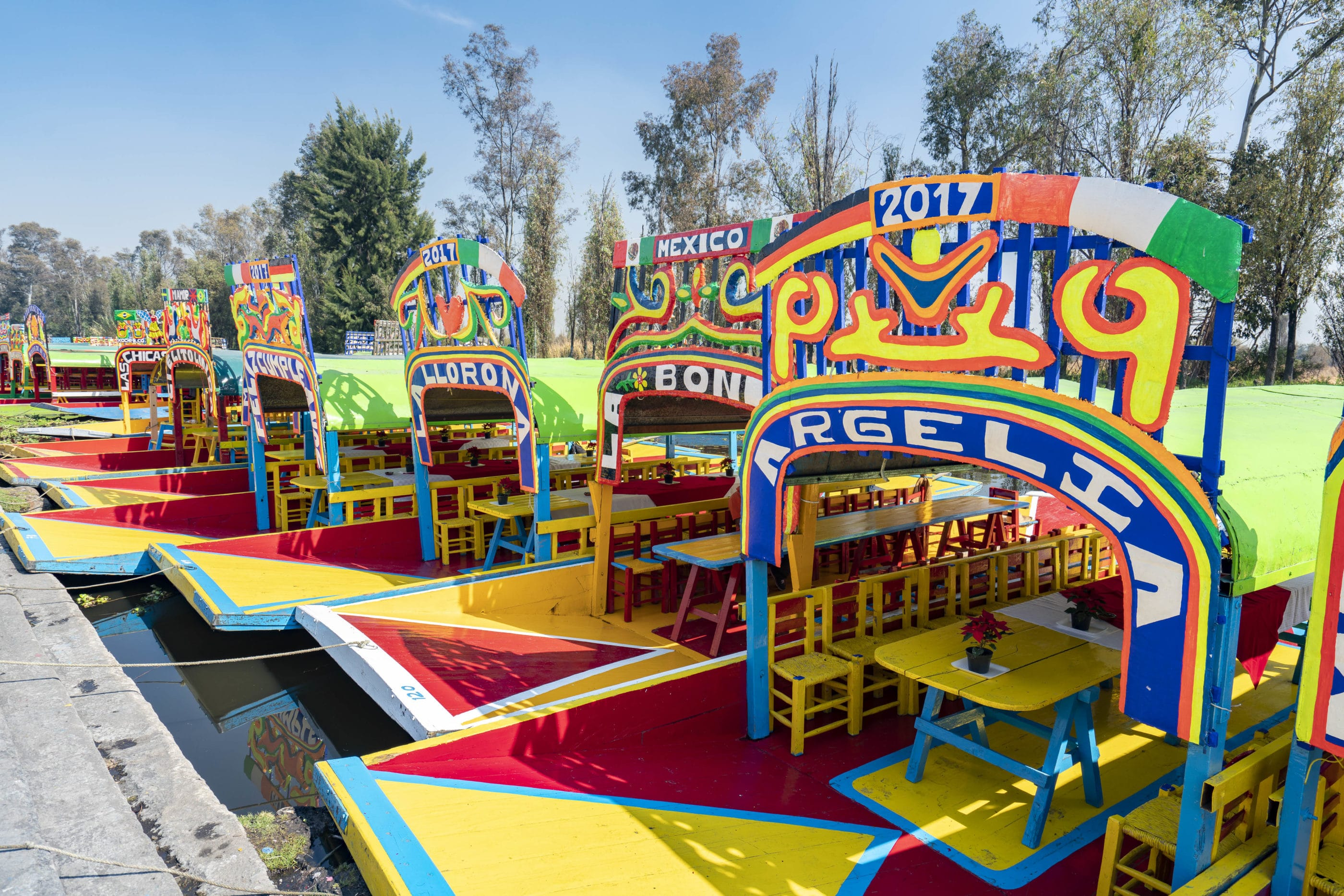 Colorful trajinera boats lined up next to each other on the water at Xochimilco.