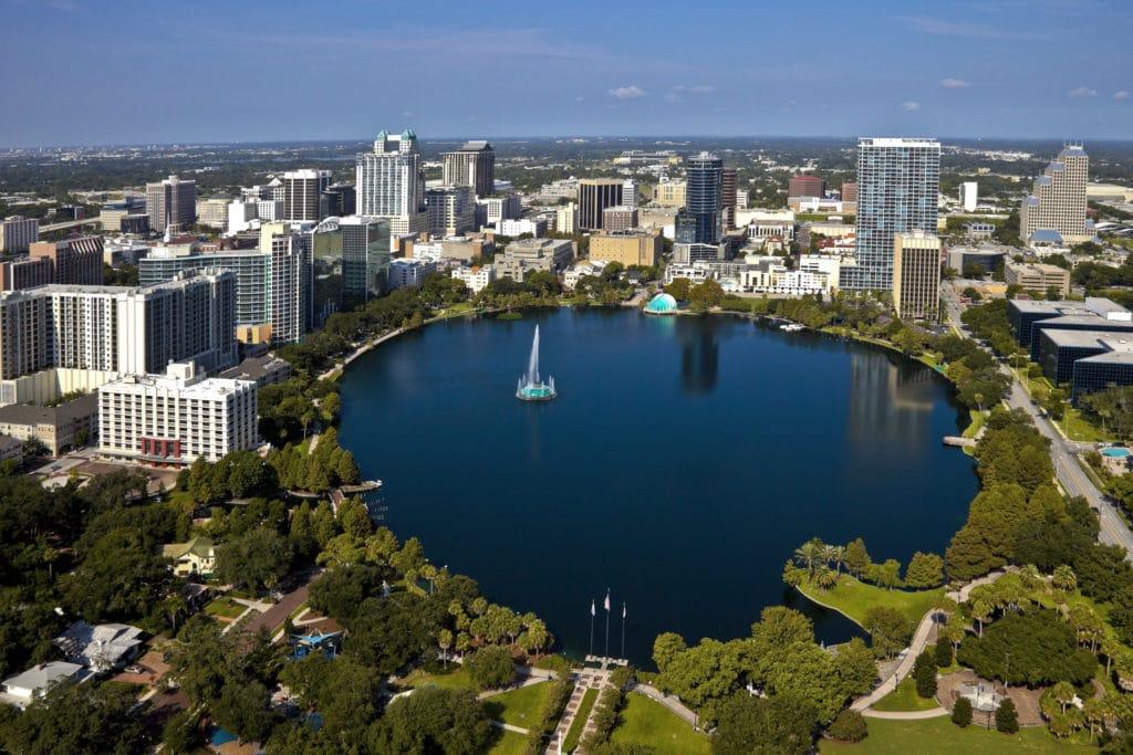Vue aérienne du lac Eola avec entouré d'espaces verts et de bâtiments de la ville en arrière-plan.