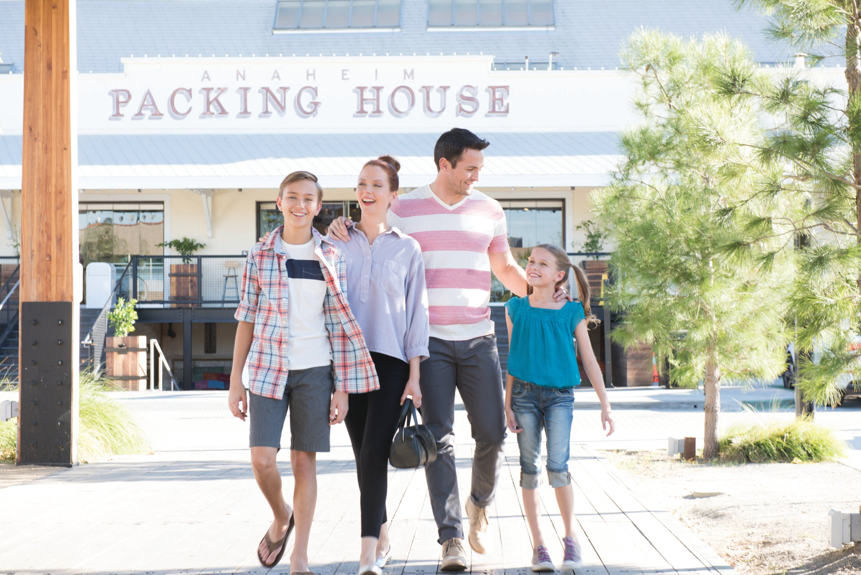 A family walks in front of Anaheim Packing House.
