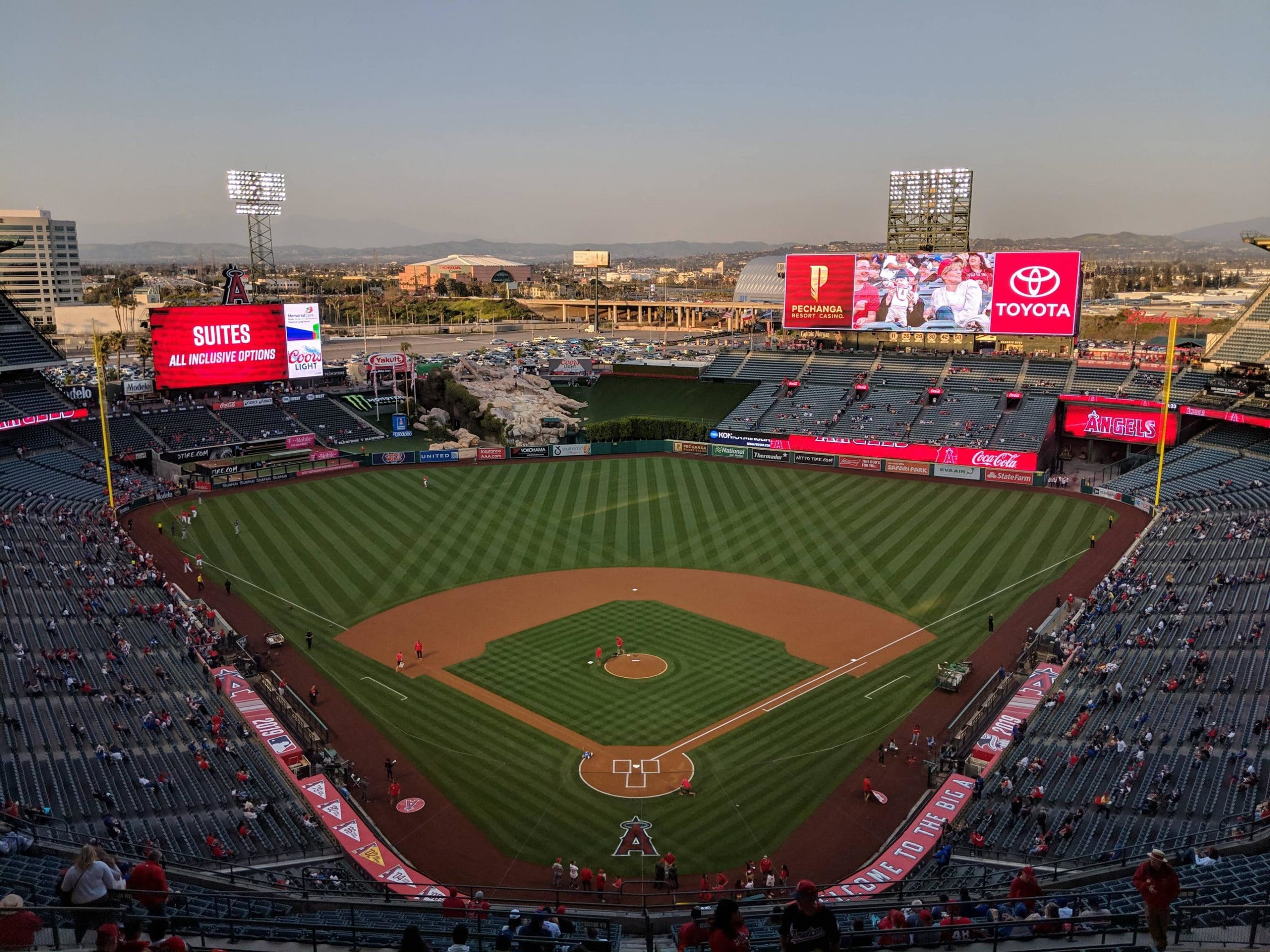 Aerial view of Angel Stadium at dusk during a baseball game.