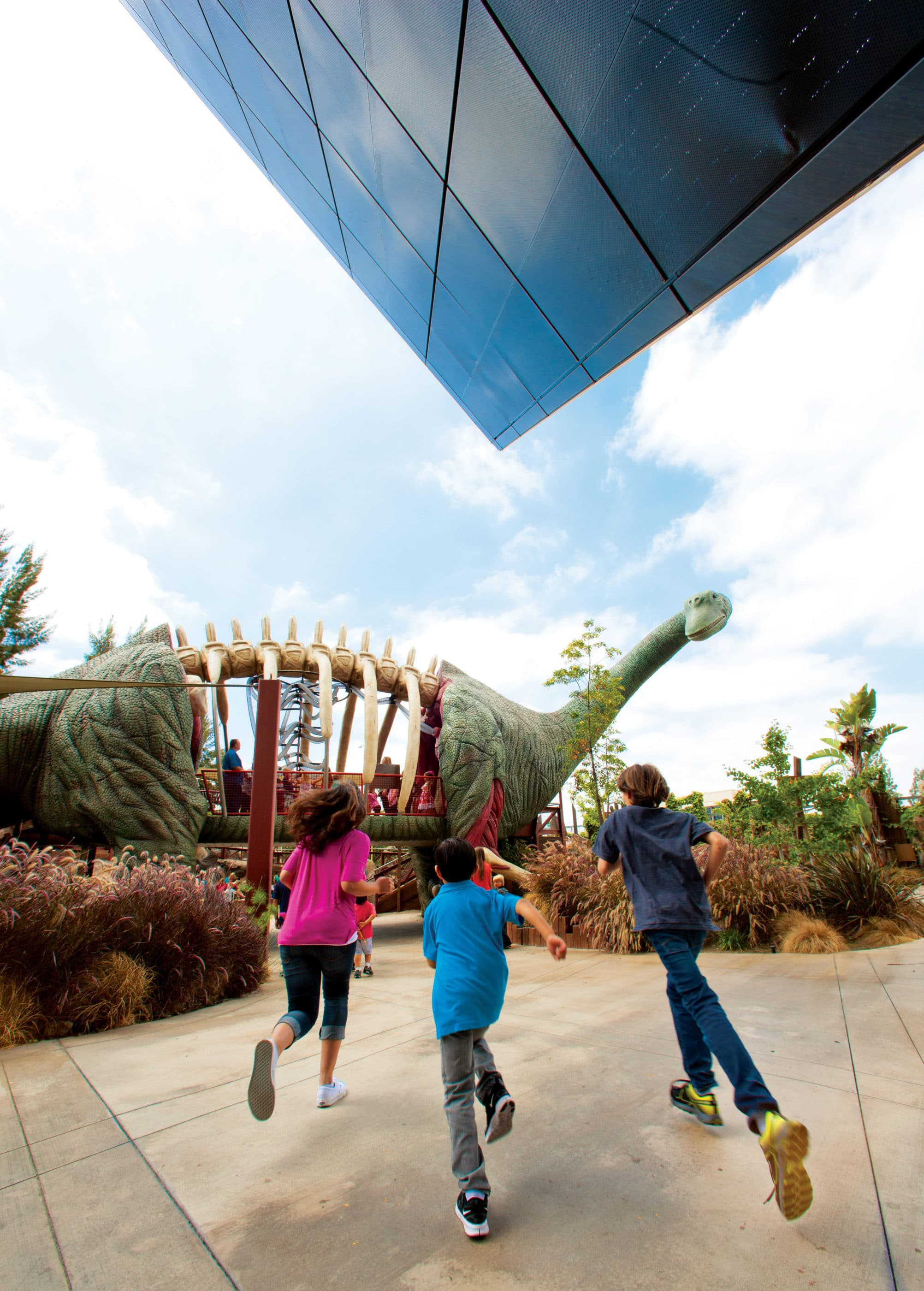 Kids run outside towards the outdoor dinosaur at The Cube in Anaheim.