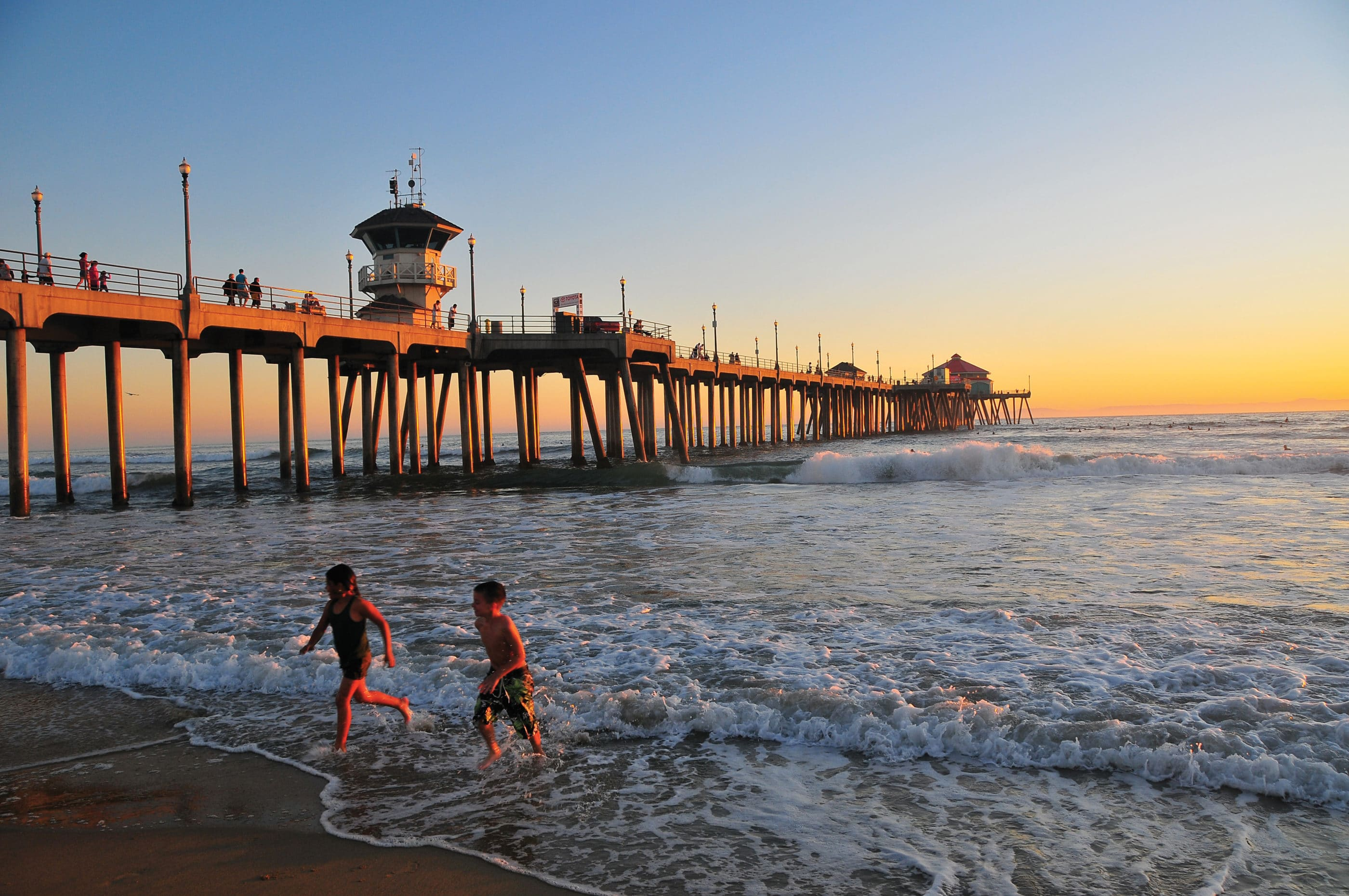 Two children run out of the ocean at sunset at Huntington Beach near the pier.