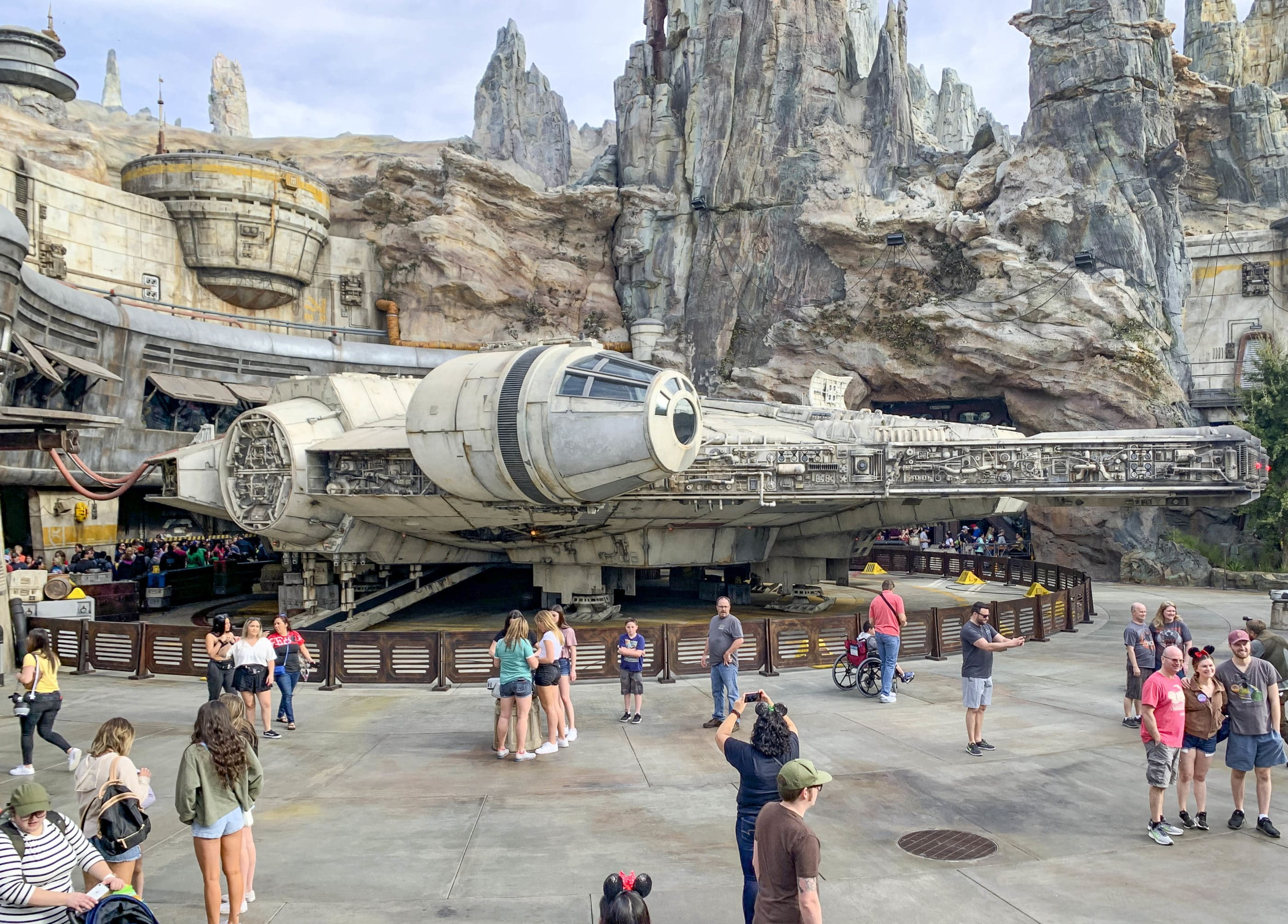 Guests take photos in front of the Millennium Falcon inside of Disneyland's Star Wars: A Galaxy's Edge.