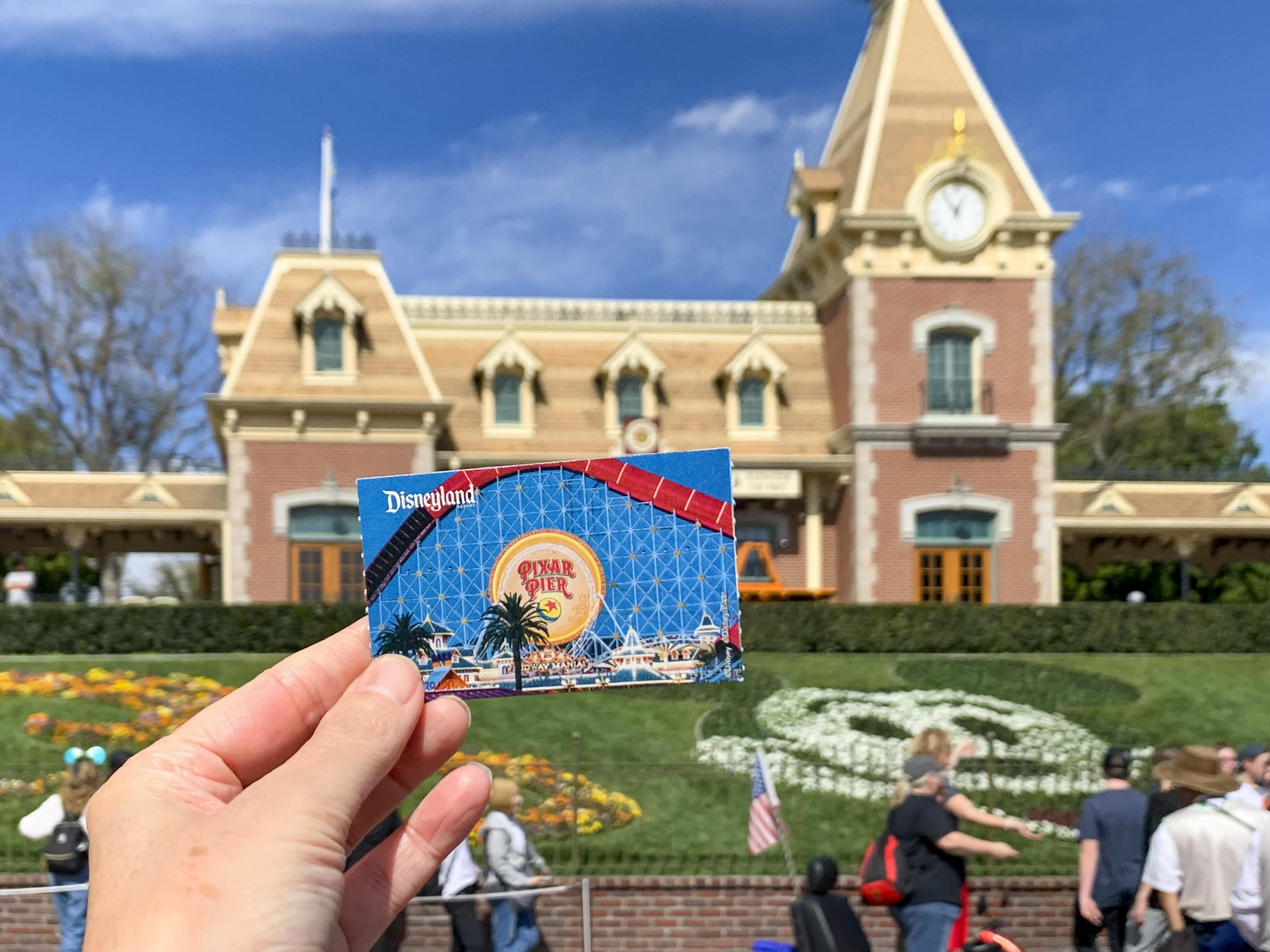 A printed Disney California ticket held up against the Main Street U.S.A. train station facade.