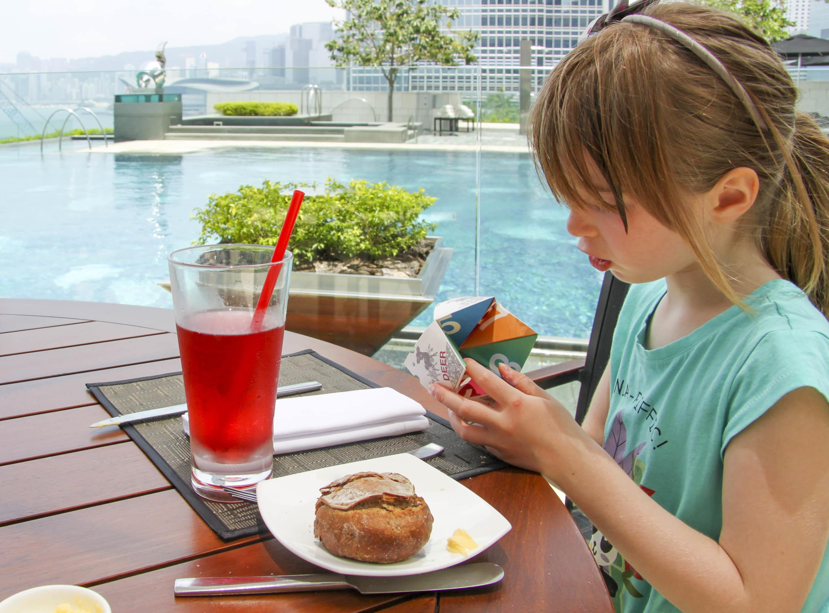 My daughter holds the paper fortune teller during lunch by the pool at Four Seasons Hong Kong.