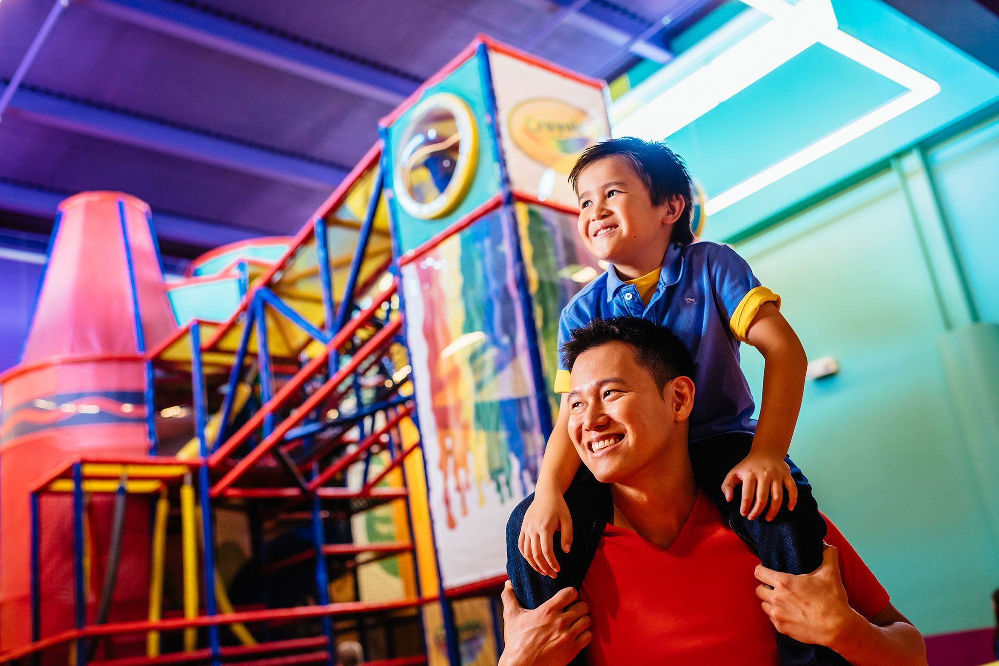 A little boy rides on the shoulders of a man as they explore Crayola Experience Orlando.