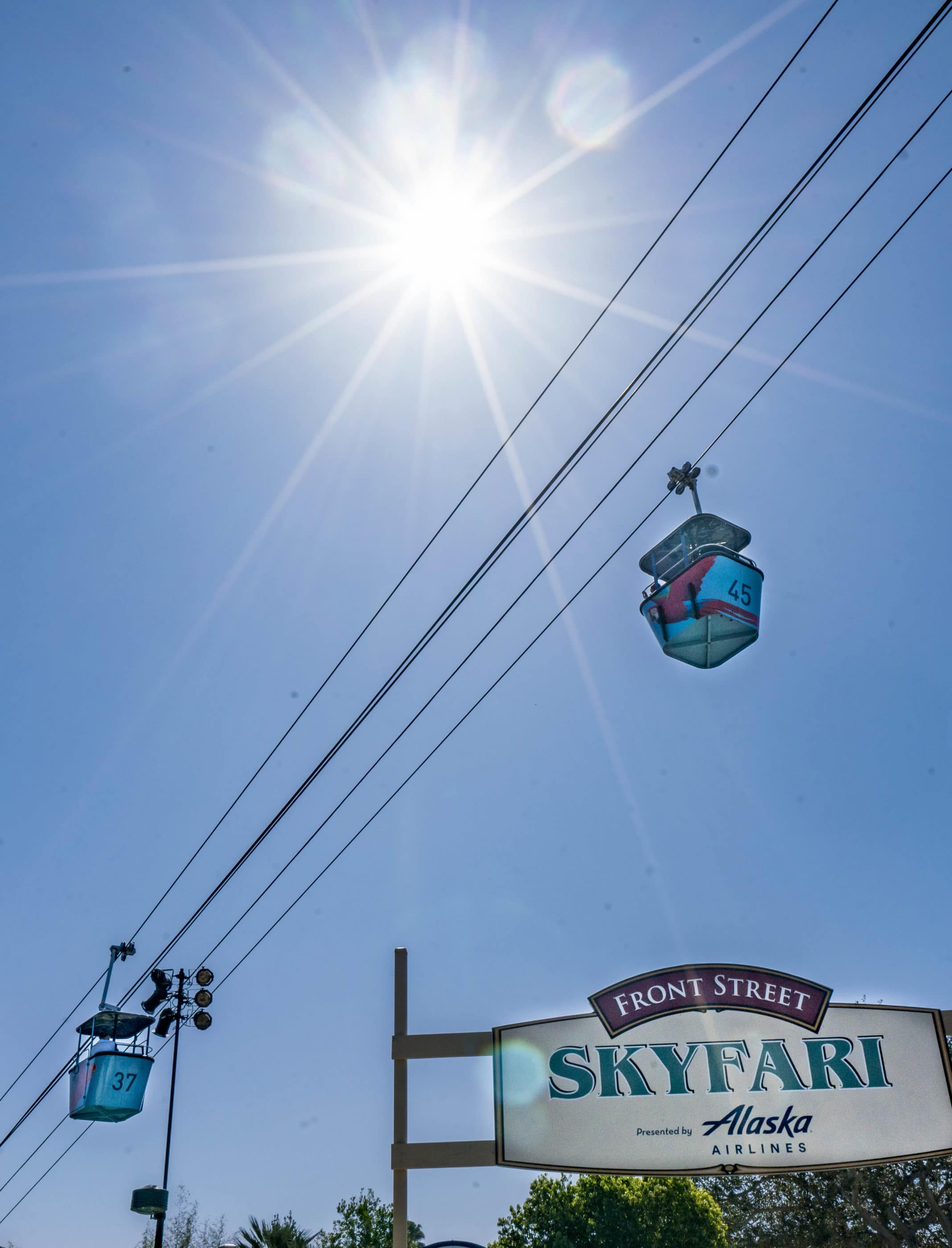 Upward view of two Skyfari aerial trams against a blue morning sky.