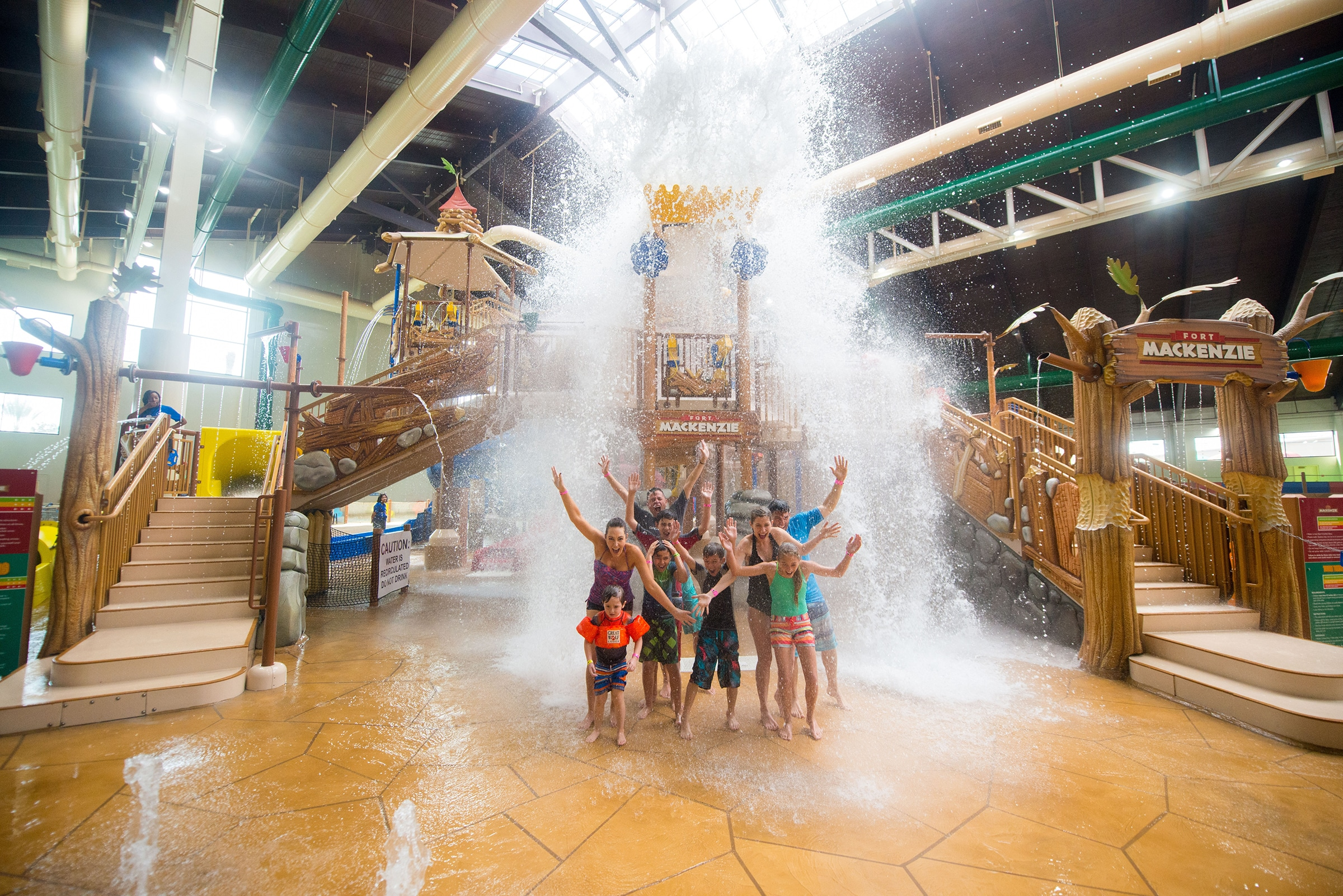 Kids pose happy in front of a Fort Mackenzie water play area inside of Great Wolf Lodge