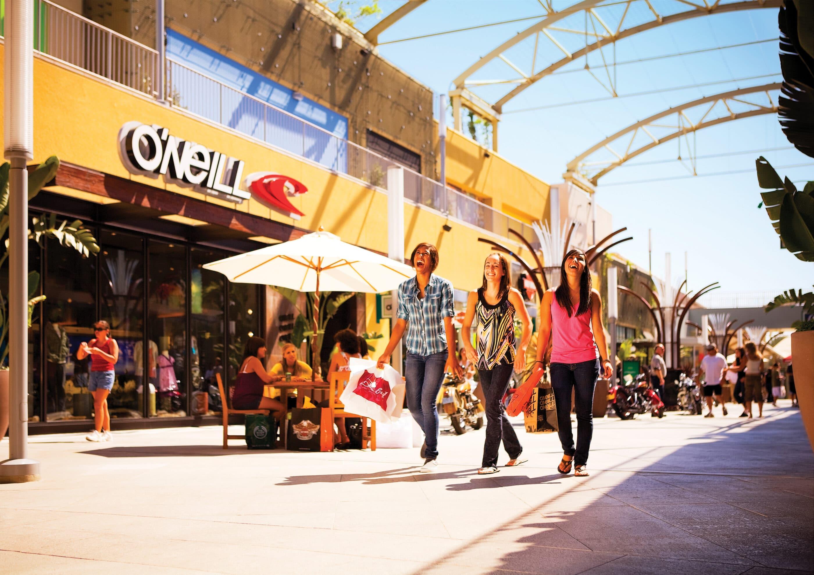 Friends walk on a sunny day past stores at Anaheim GardenWalk.