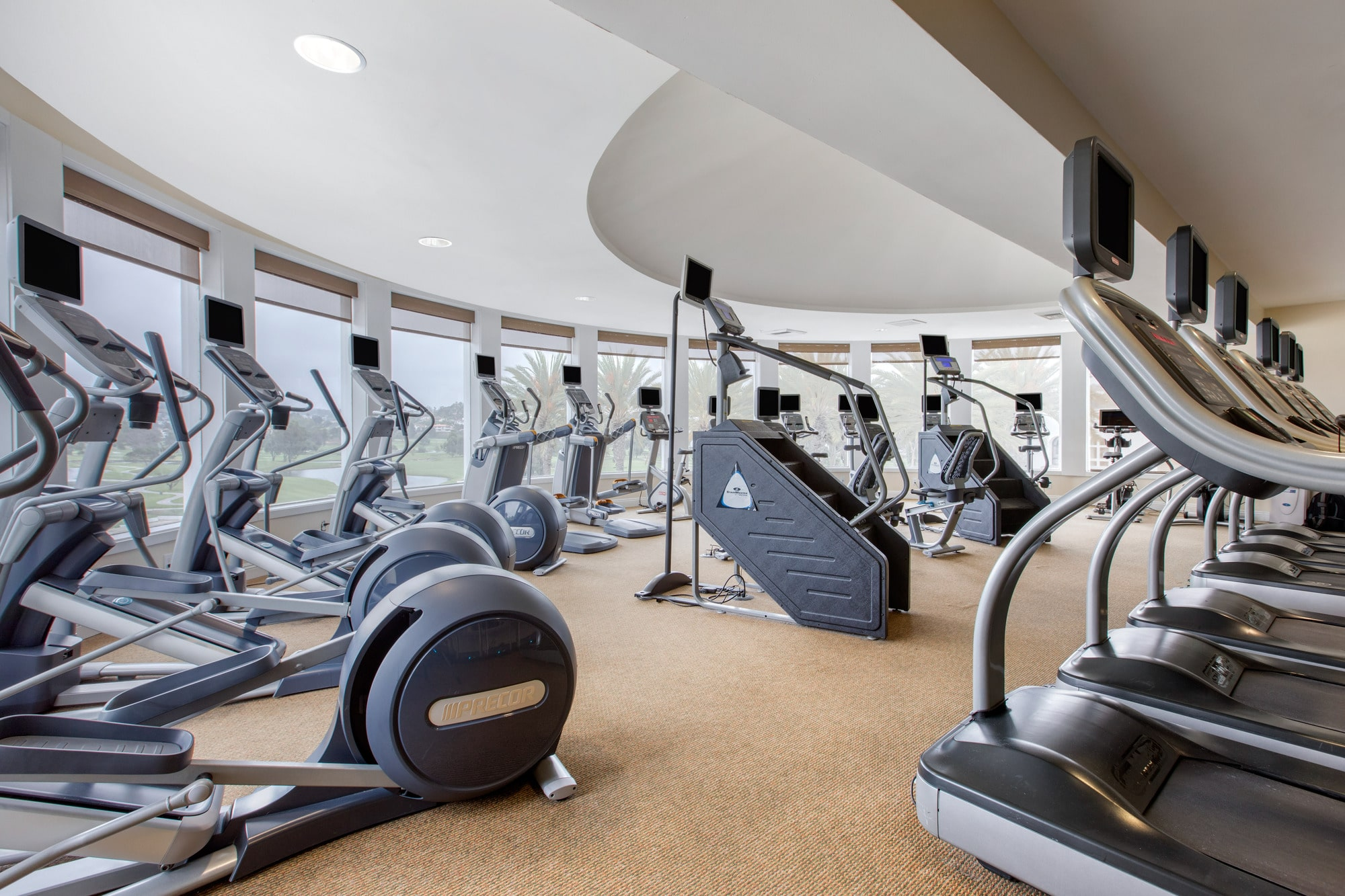 Cardio equipment inside the Athletic Club with views over the golf course.