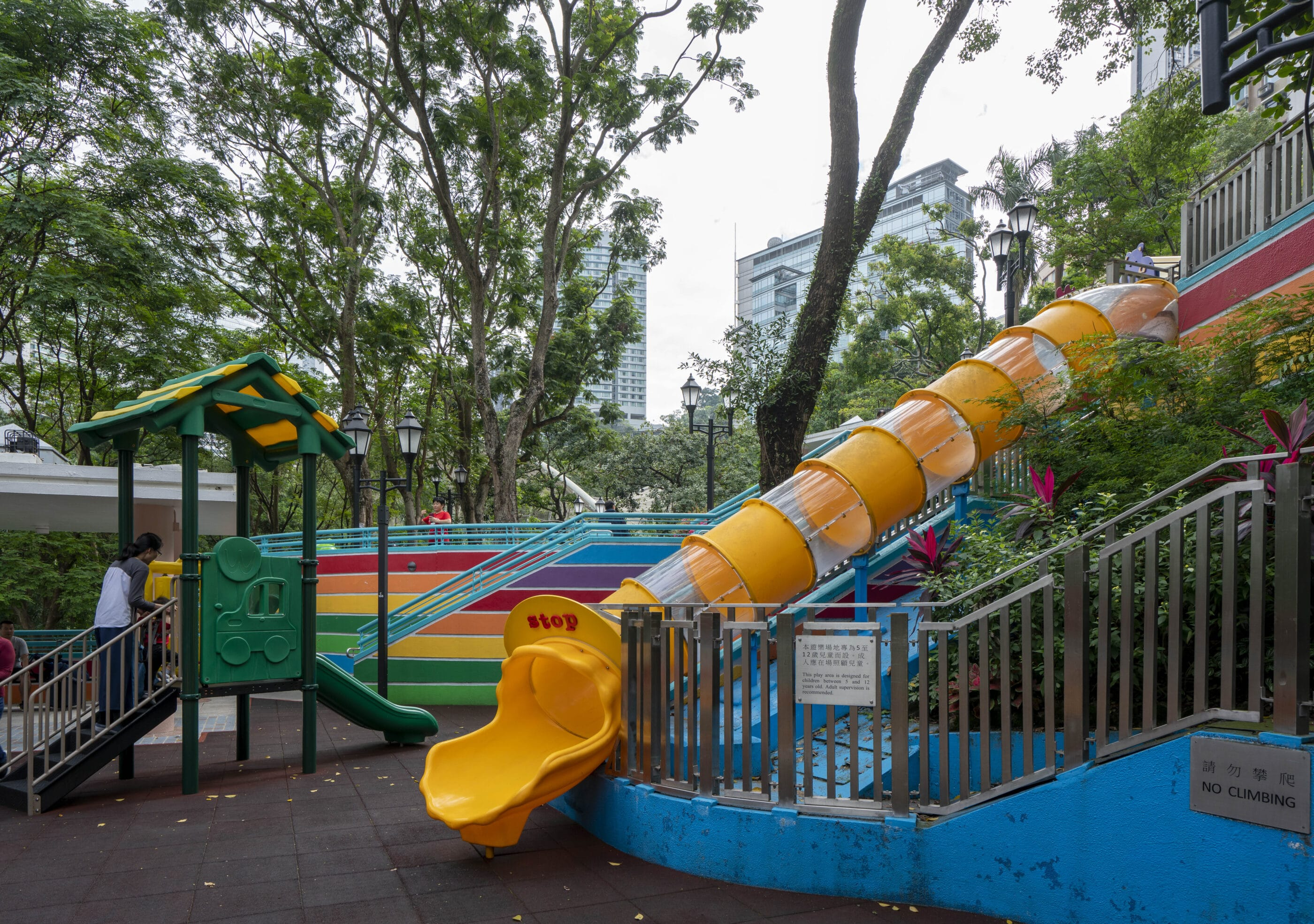 A large tunnel slide and part of the colorful play structure at the Hong Kong Park playground.