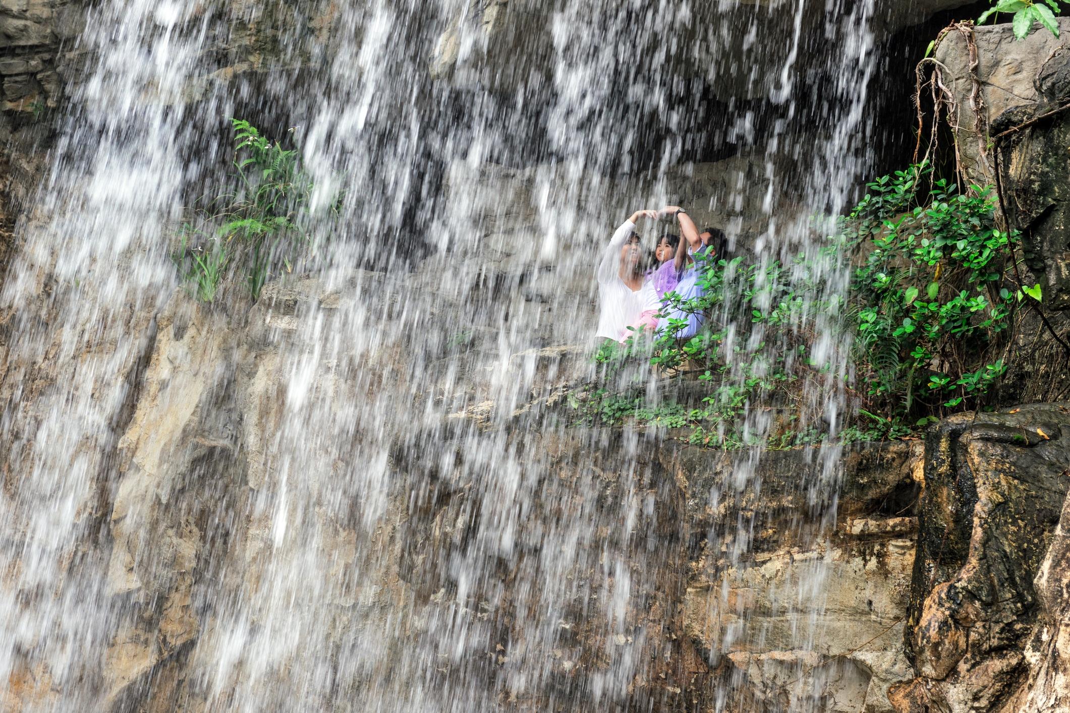 A family walks under the waterfall at Hong Kong Park.