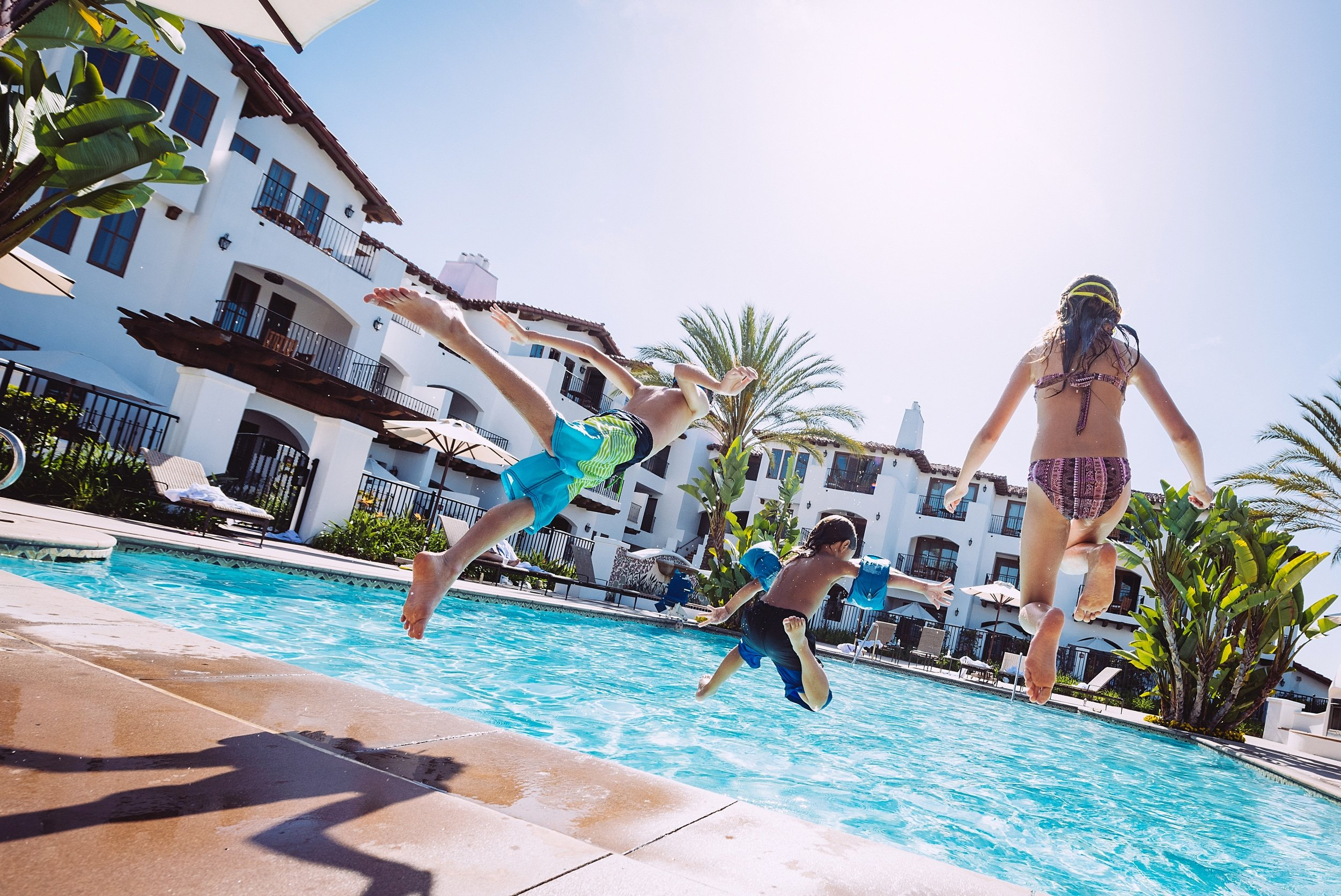 Kids jump into the Villa Pool on a sunny day at Omni La Costa.