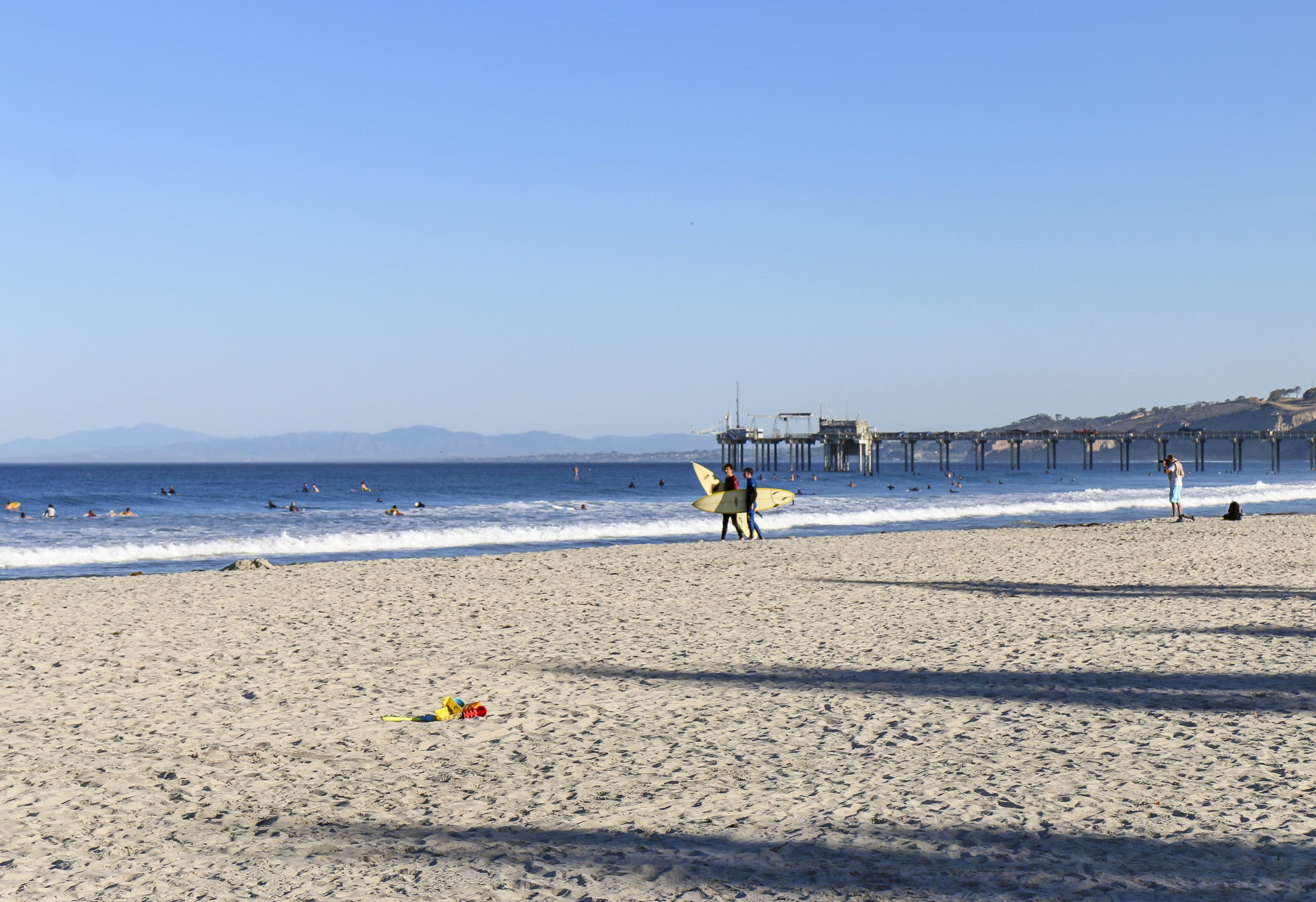Two surfers walk on the sand on an October morning at La Jolla Shores Beach.