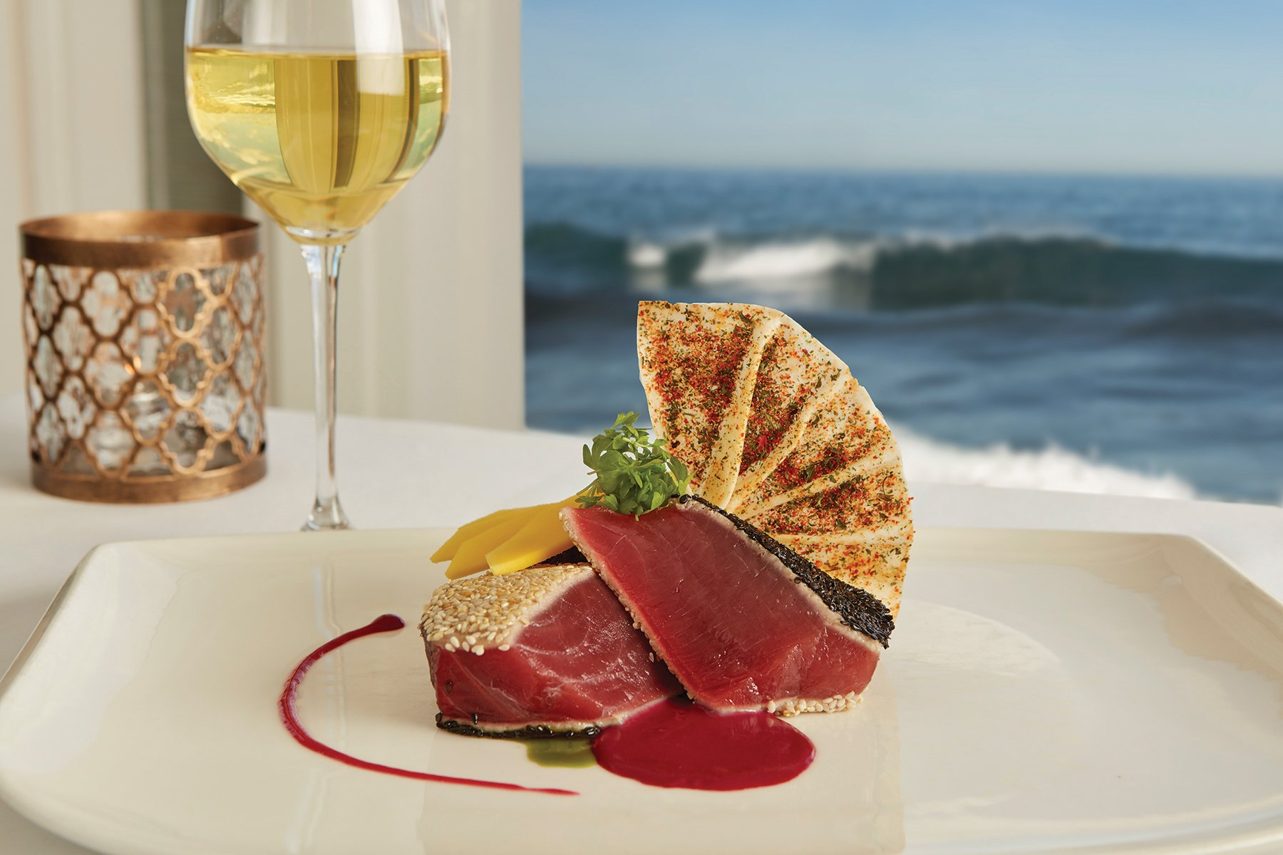 Seared ahi and a glass of white wine against the window with the ocean behind.