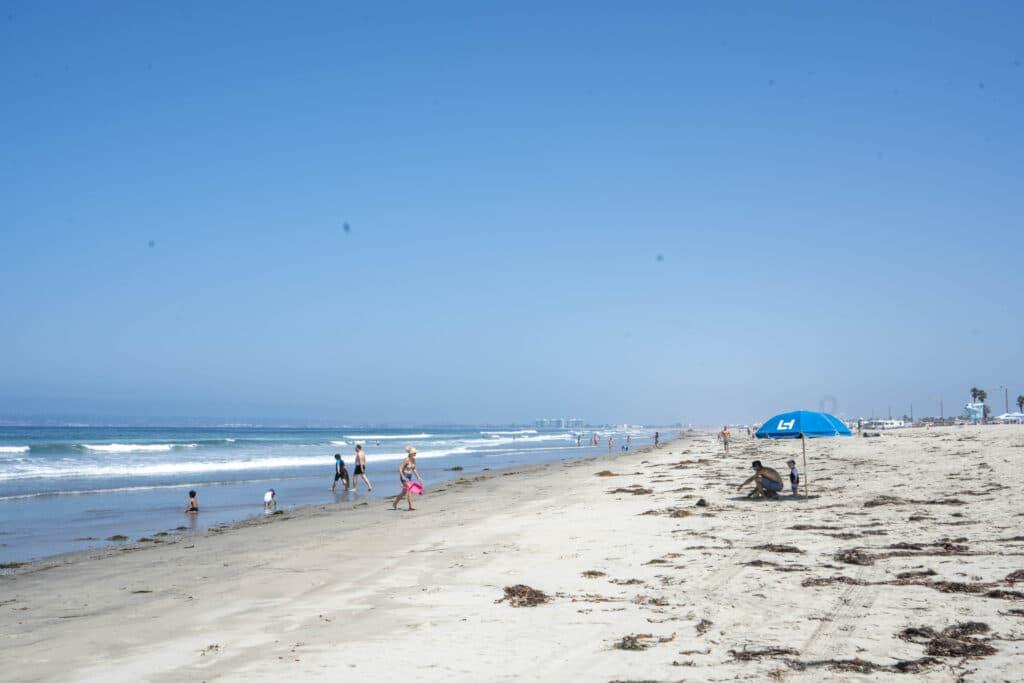 A Loews Coronado Bay Resort umbrella in the sand on Silver Strand State Beach.