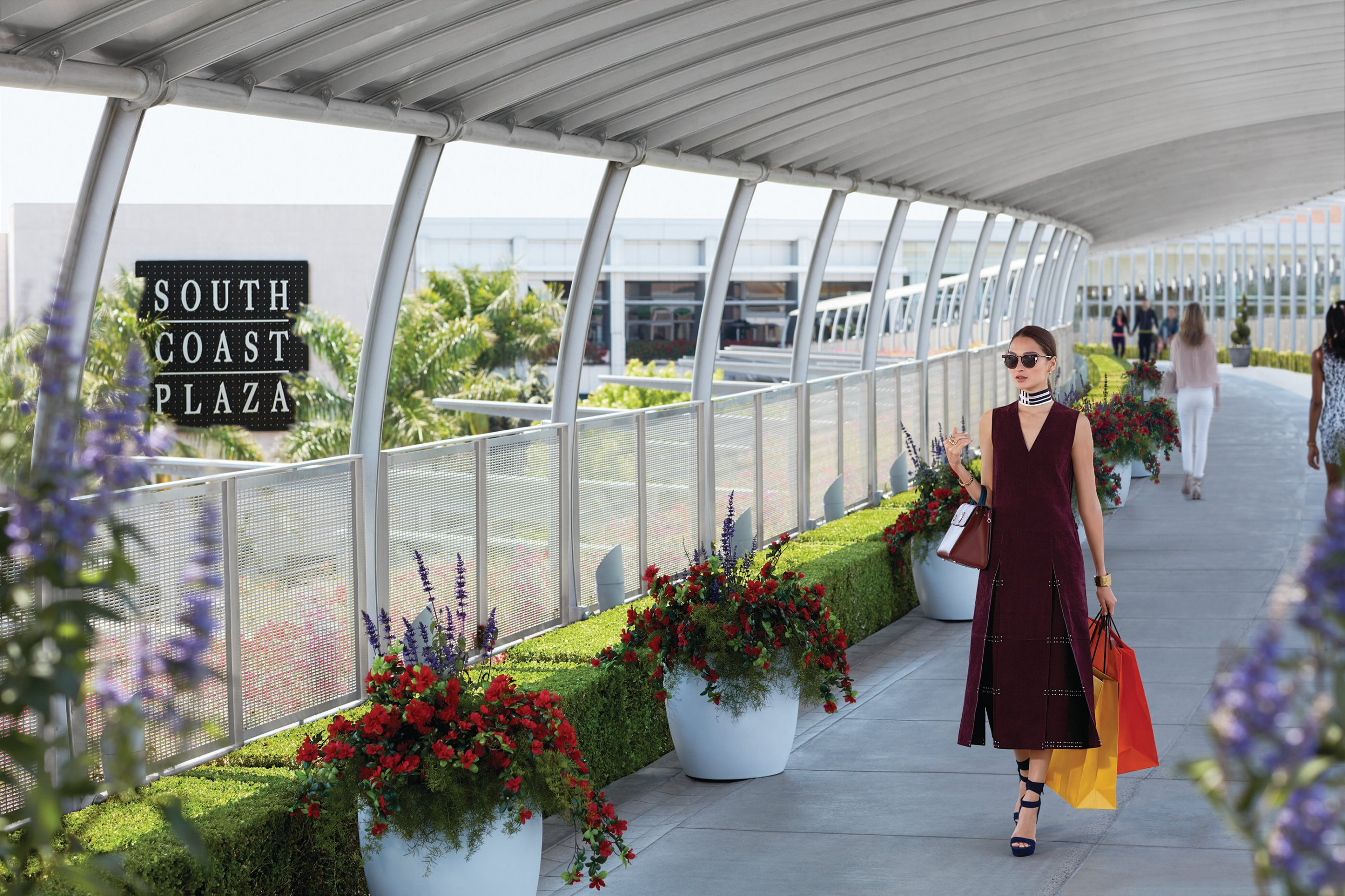 A women exits the mall down an elevated pathway carrying shopping bags at South Coast Plaza.