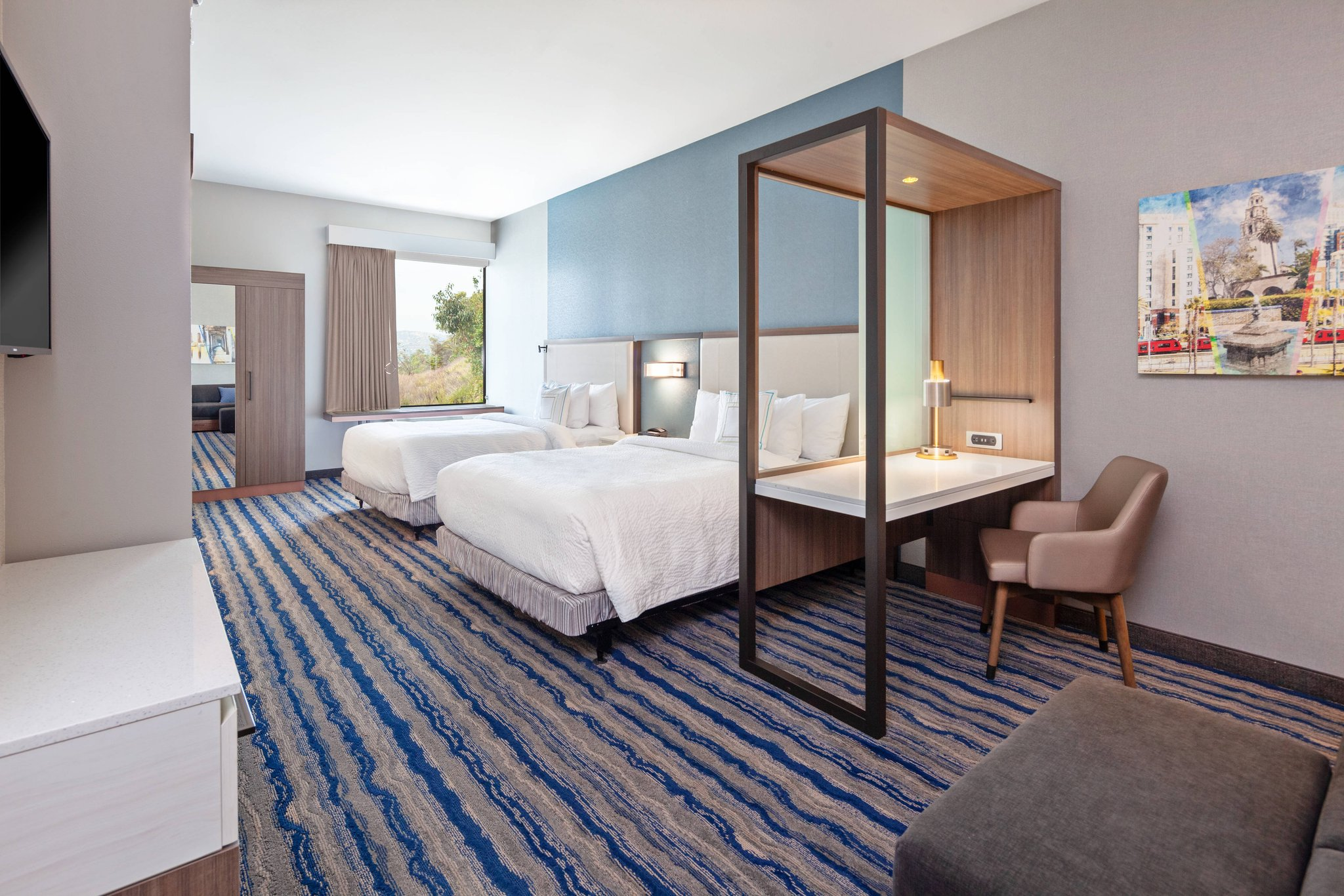 A contemporary double bed room with seating area and desk at Springhill Suites Escondido near San Diego Safari Park.