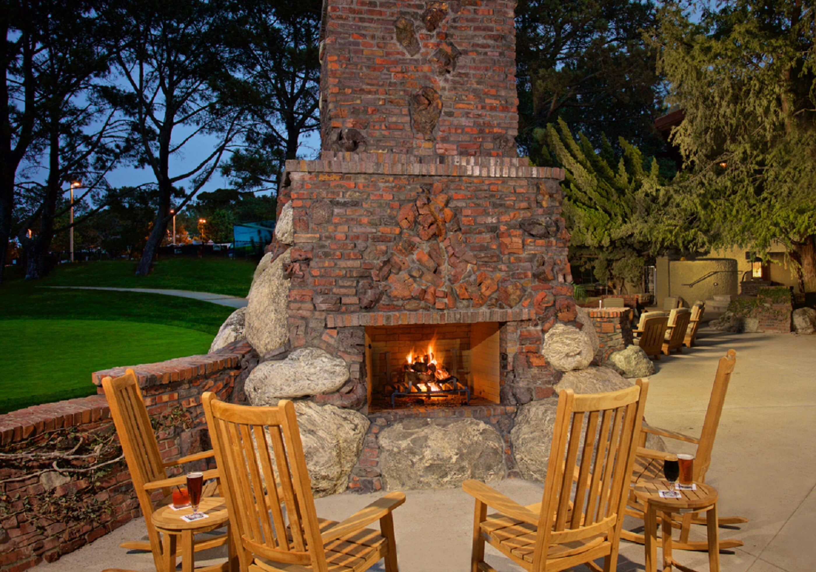 Wooden rocking chairs surround an outdoor brick fireplace on the terrace at The Grill restaurant at The Lodge at Torrey Pines.