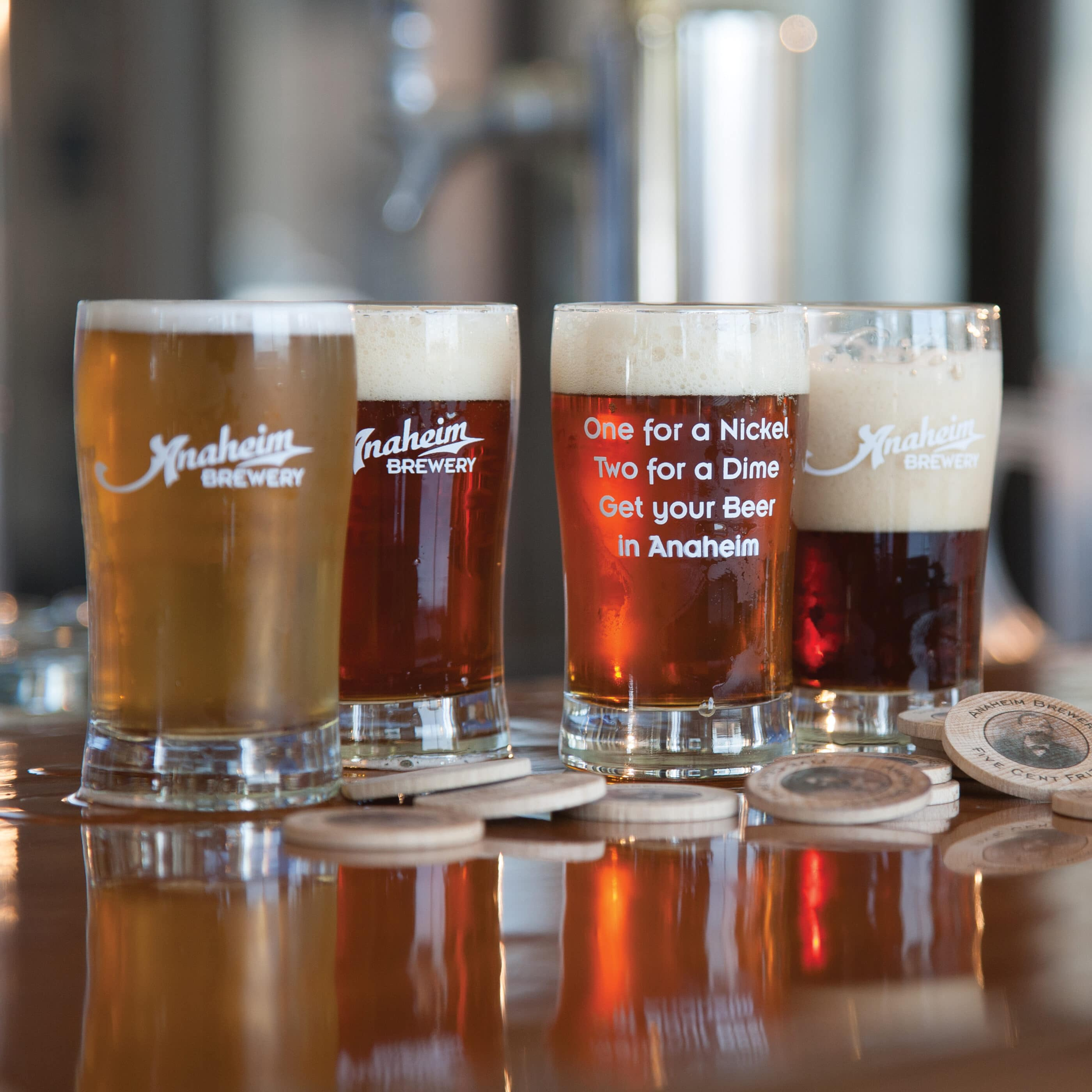 Four freshly-poured Anaheim Brewery pints on a table.