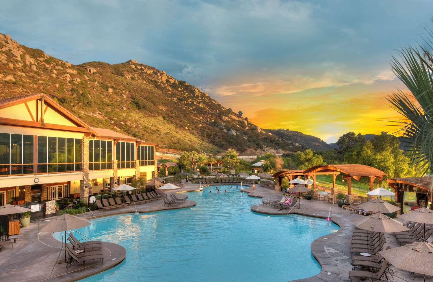 People enjoy a swimming pool at Welk Resorts San Diego at sunset.