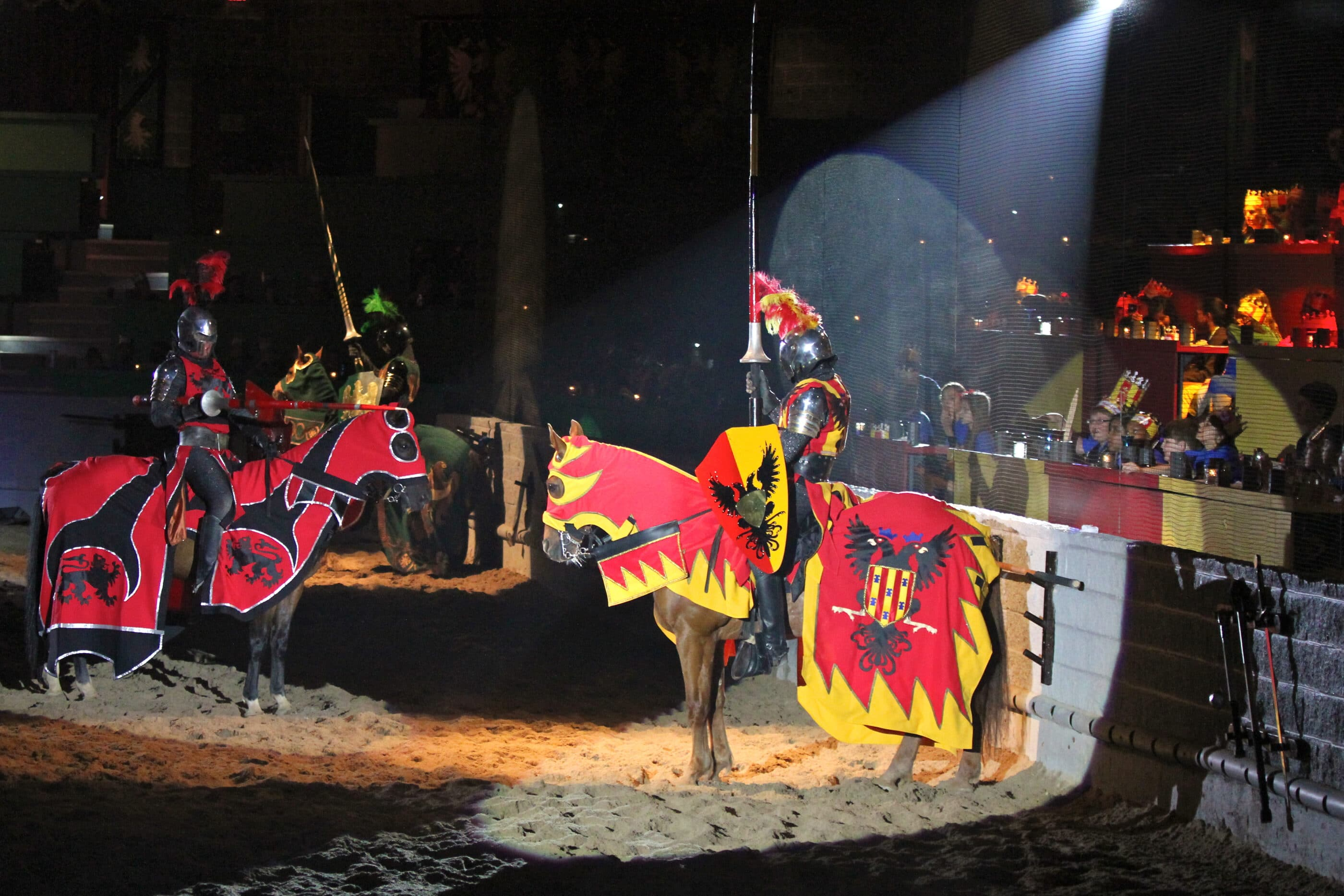 Knights on horses face each other in the arena as diners watch at Medieval Times.