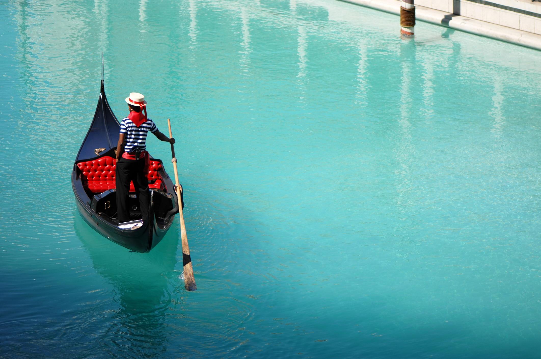 A gondolier paddles a gondola through a canal in a Venetian hotel.