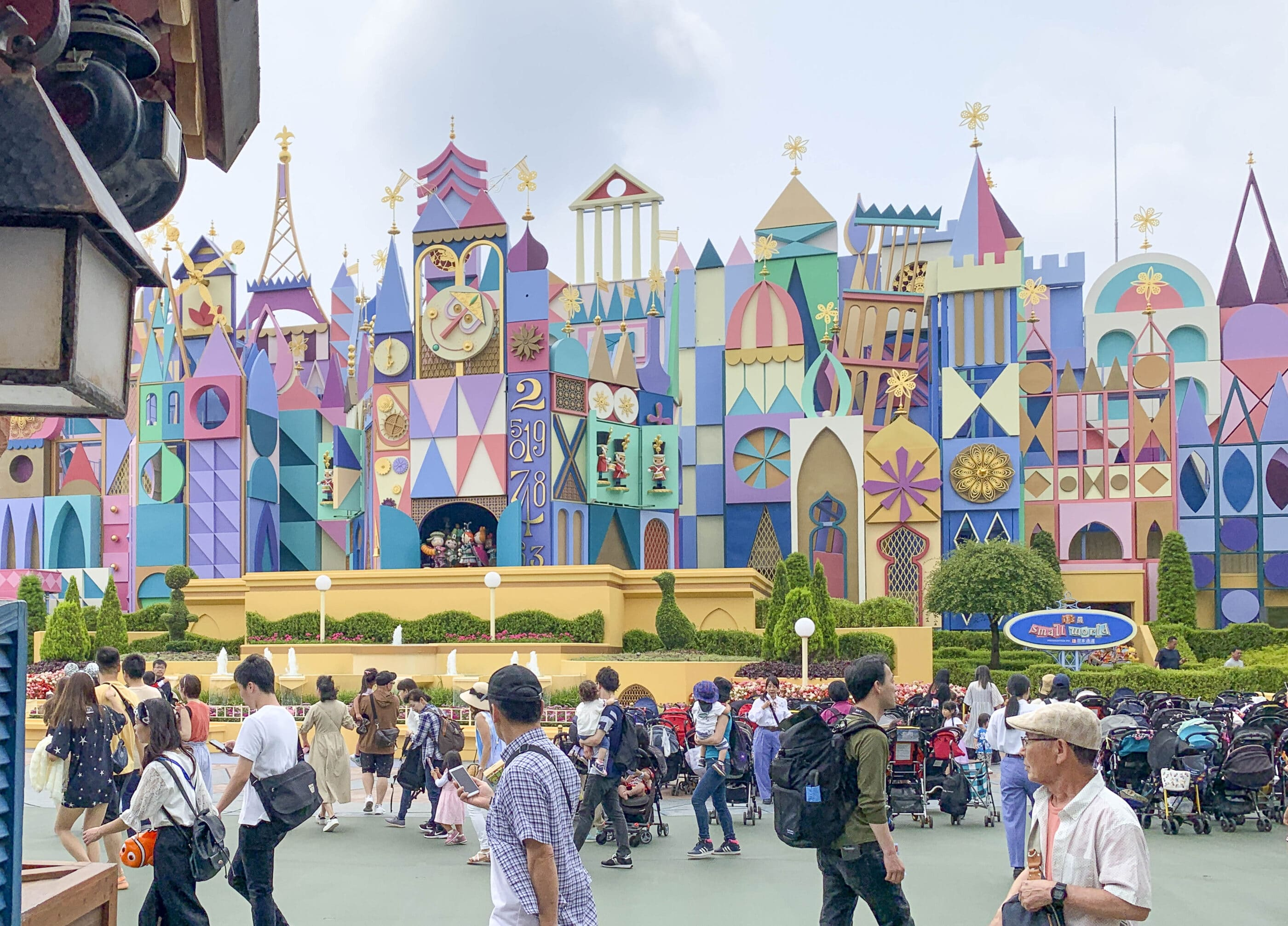 """Guests walk around Tokyo Disneyland in front of """"it's a small world."""""""