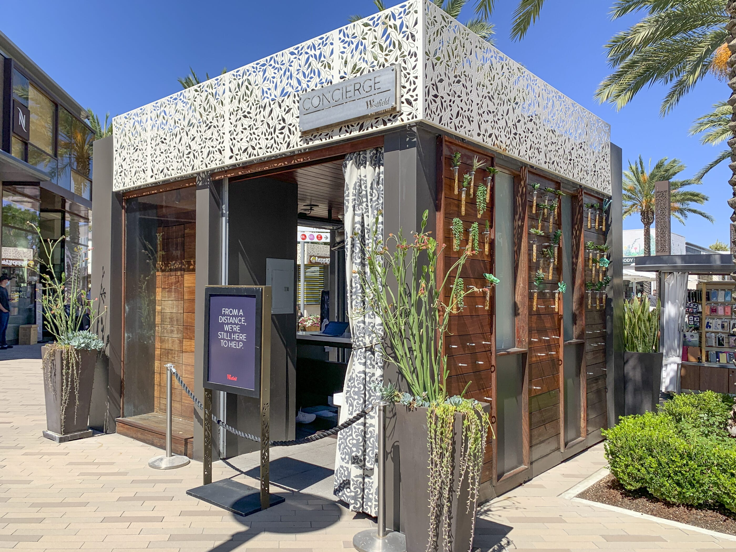 The concierge kiosk at Westfield UTC mall in La Jolla surrounded by succulent planters.
