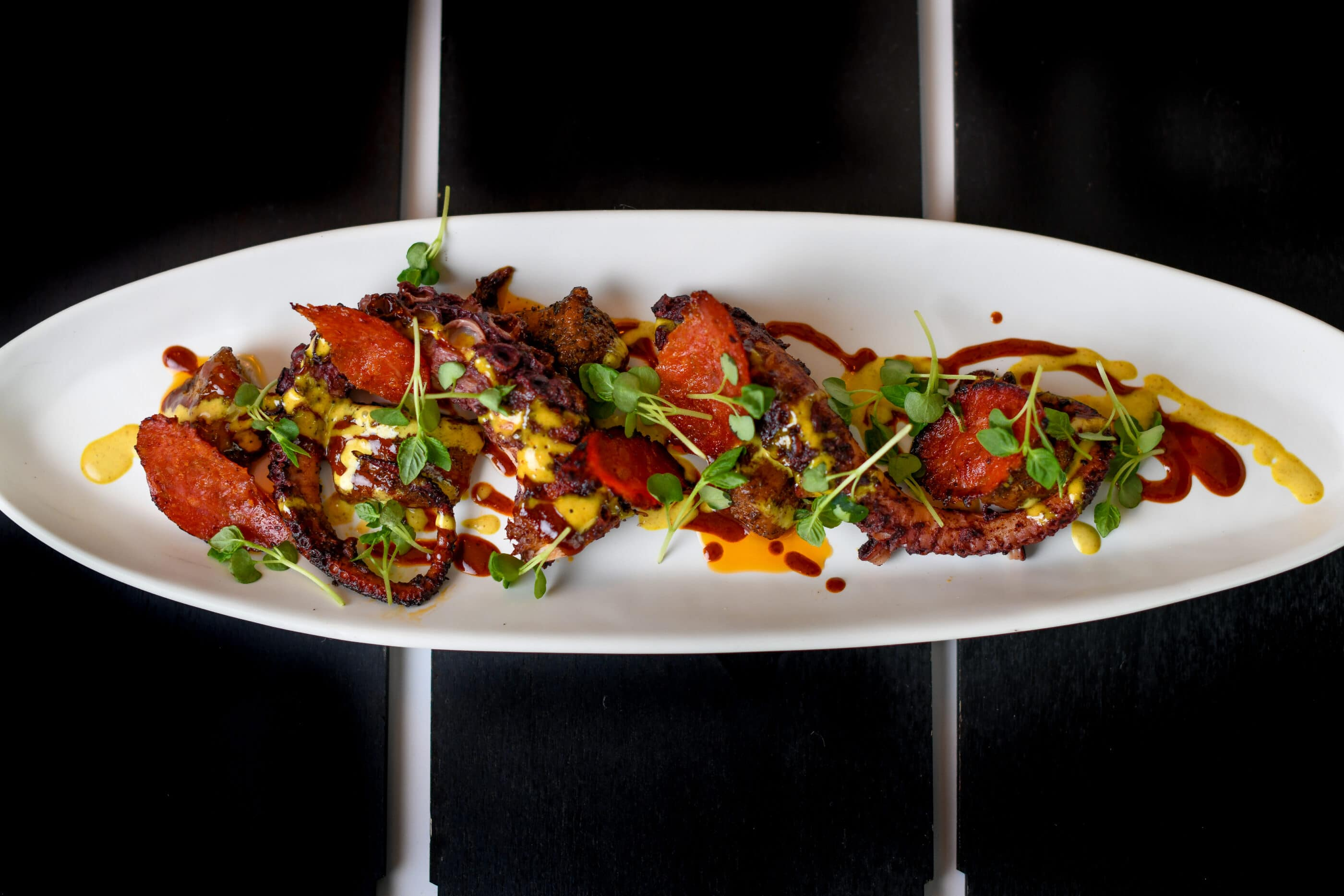A Grilled Octopus dish on a white plate a The Guild Hotel