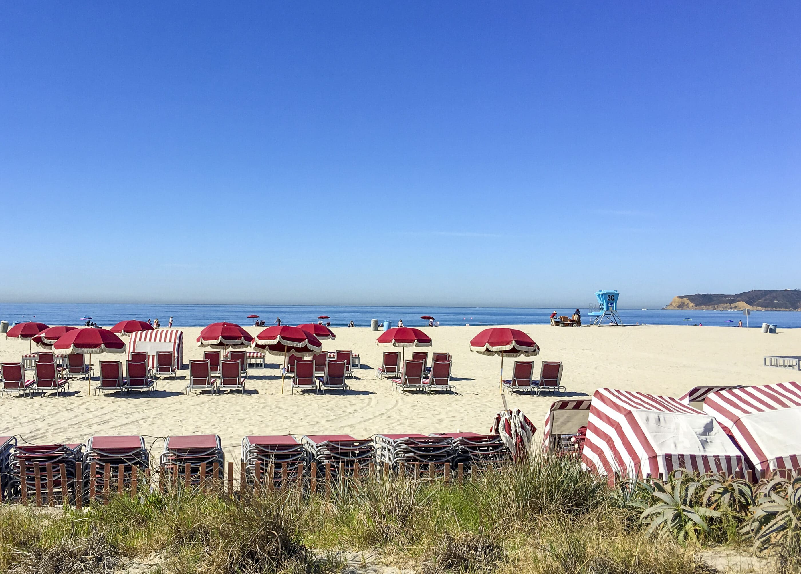 Red beach chairs in the sand in front of Hotel del Coronado.