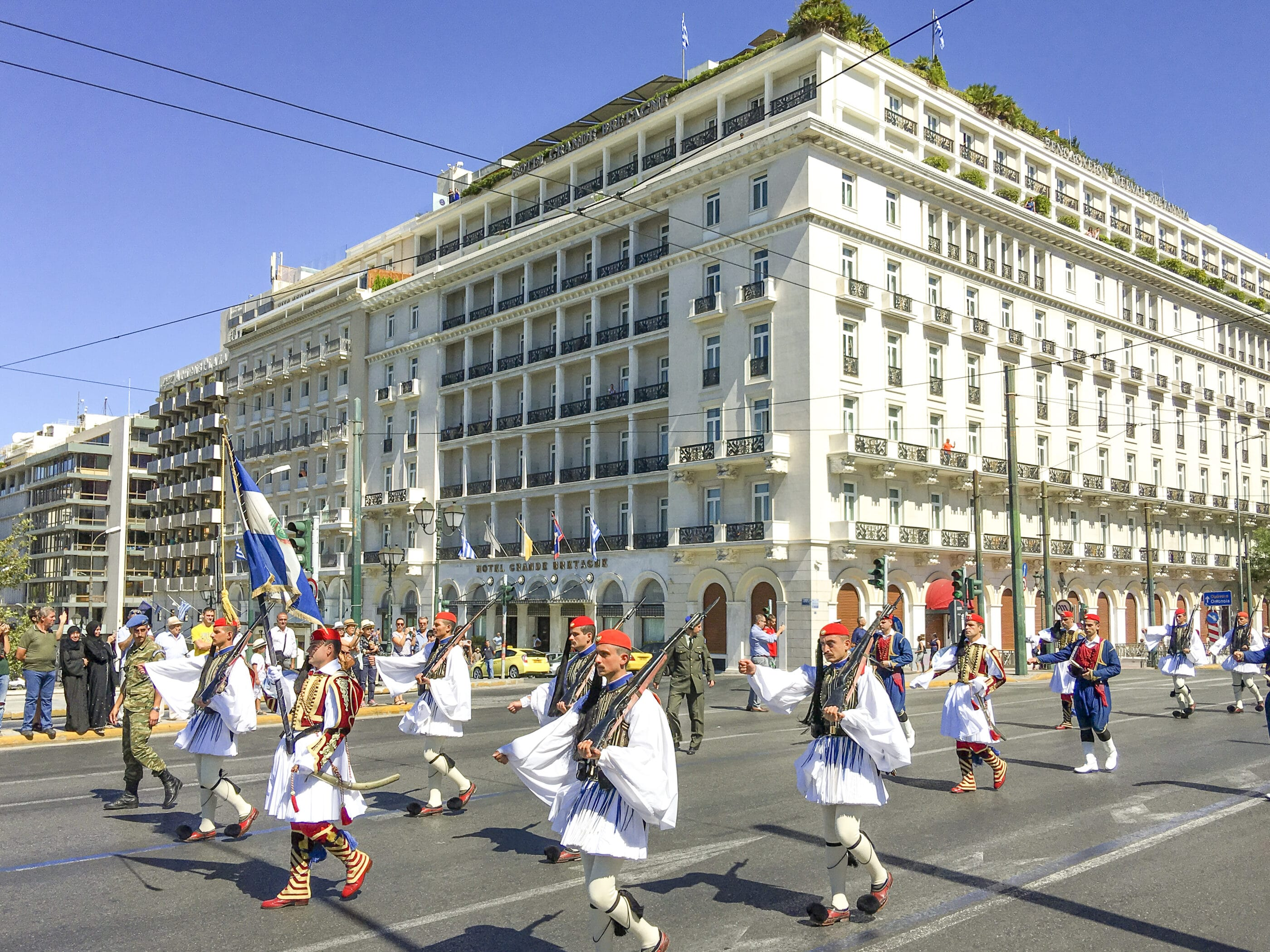 Changing of the Guards ceremony marches down the street in front of Hotel Grande Bretagne.