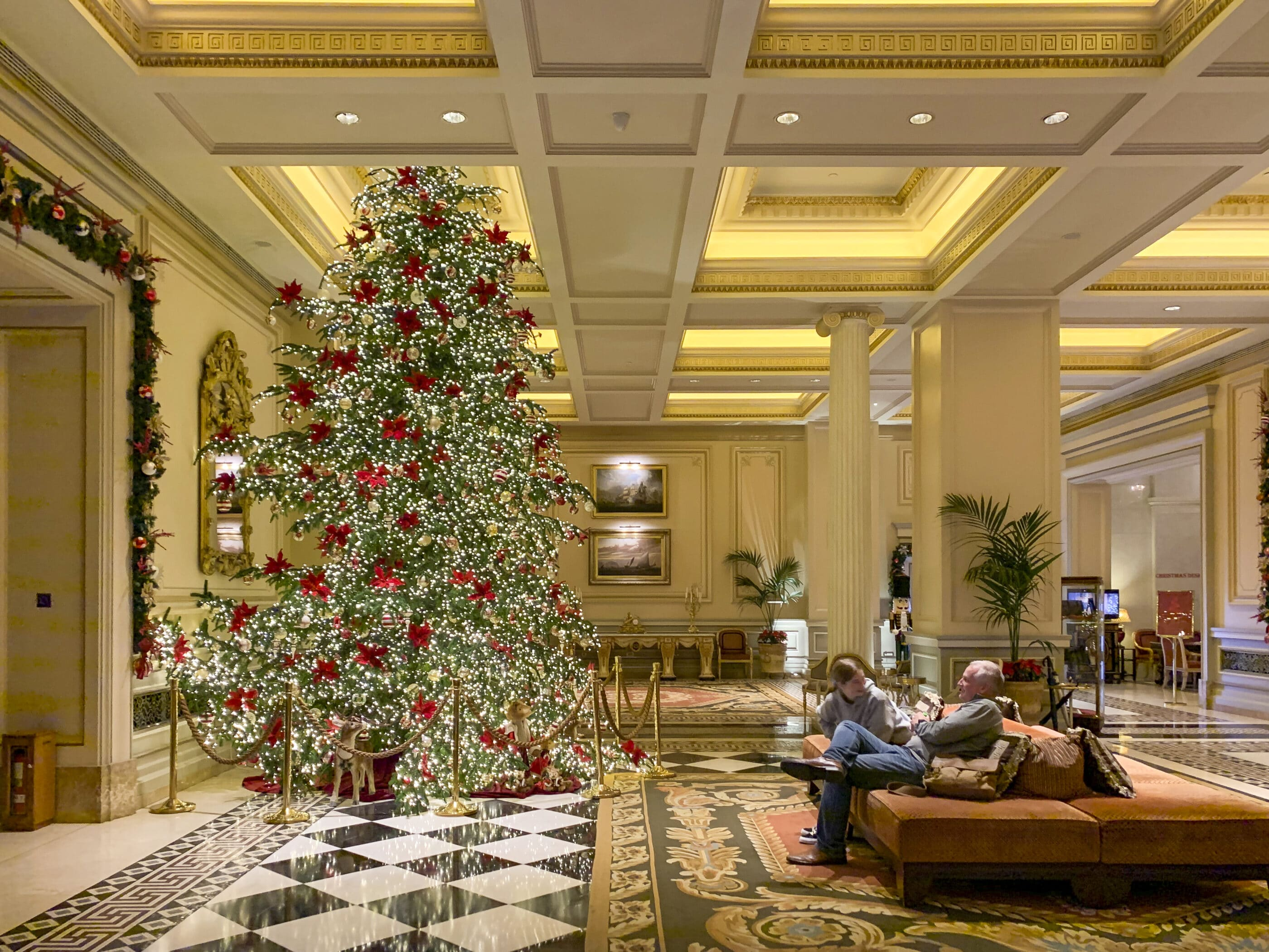 My daughter and husband sit near the lobby Christmas tree.