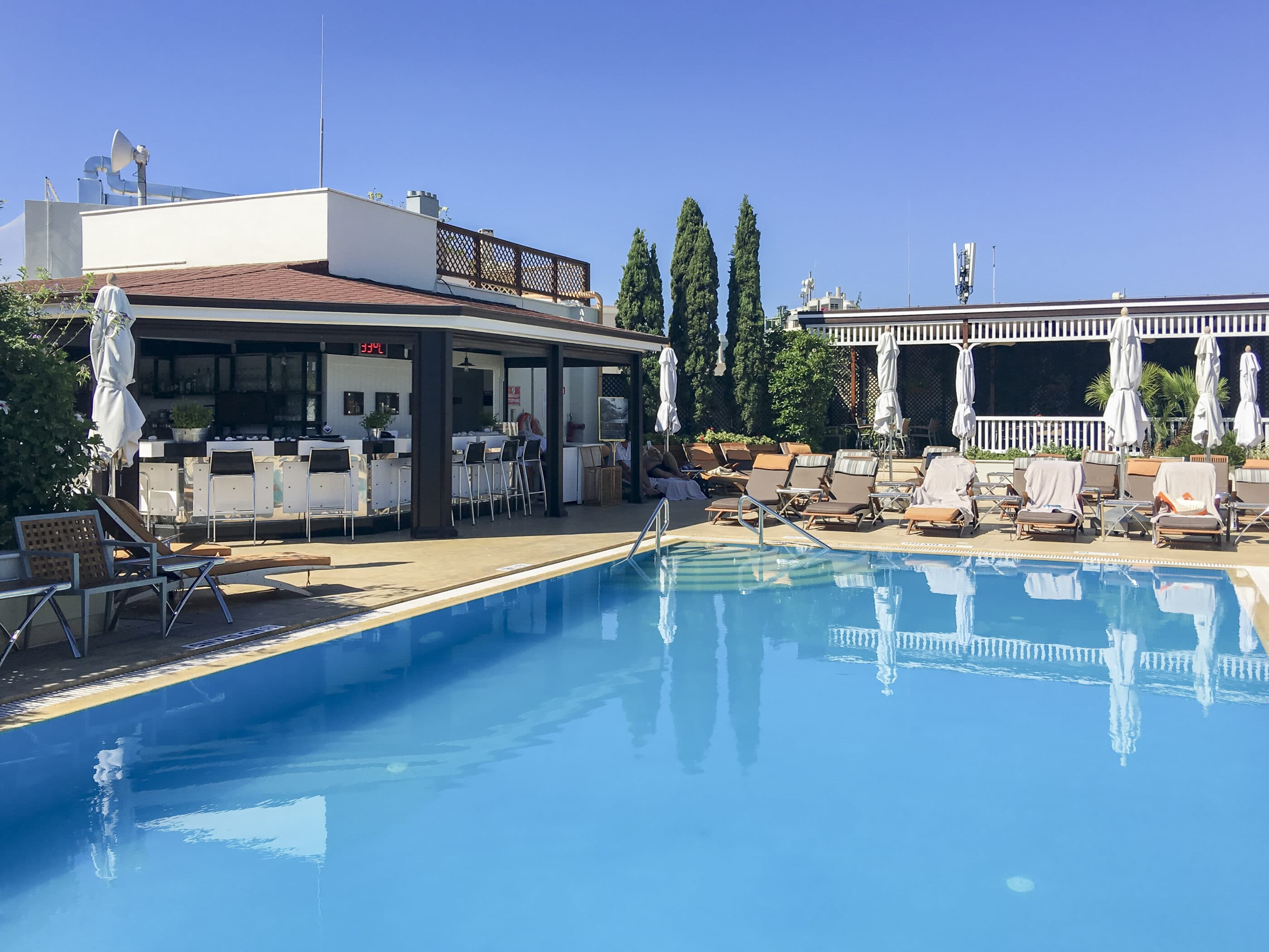 The outdoor pool on a sunny summer day in the morning before guests arrive.