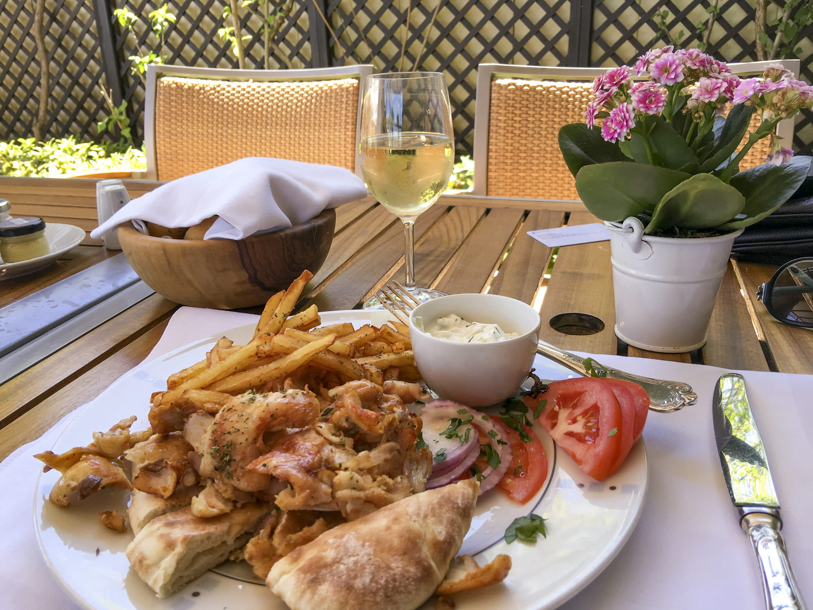 Chicken souvlaki plate with a glass of white wine at the GB Bar and Grill.
