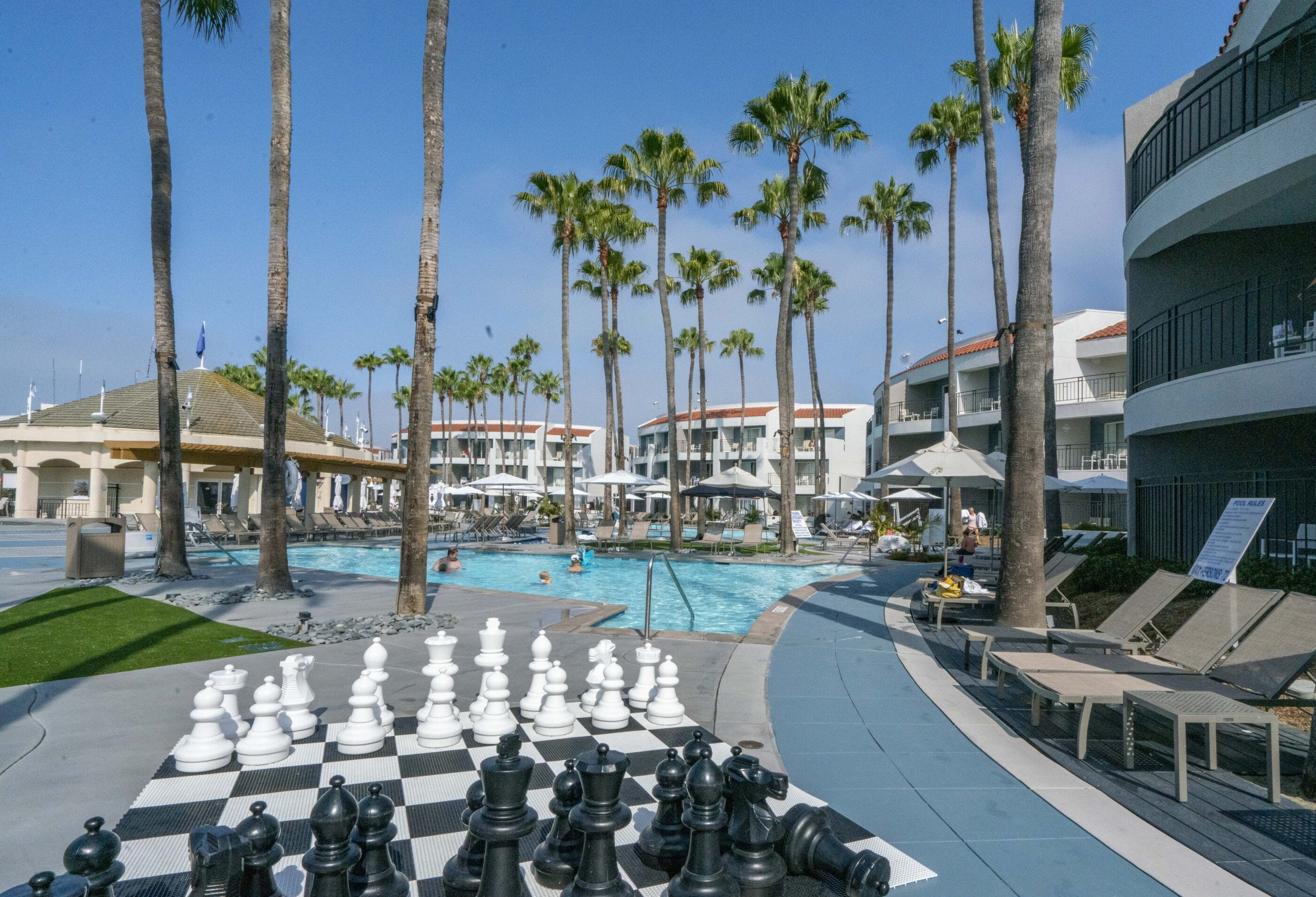 One of the three outdoor swimming pools with a large chess set near the lounge chairs.